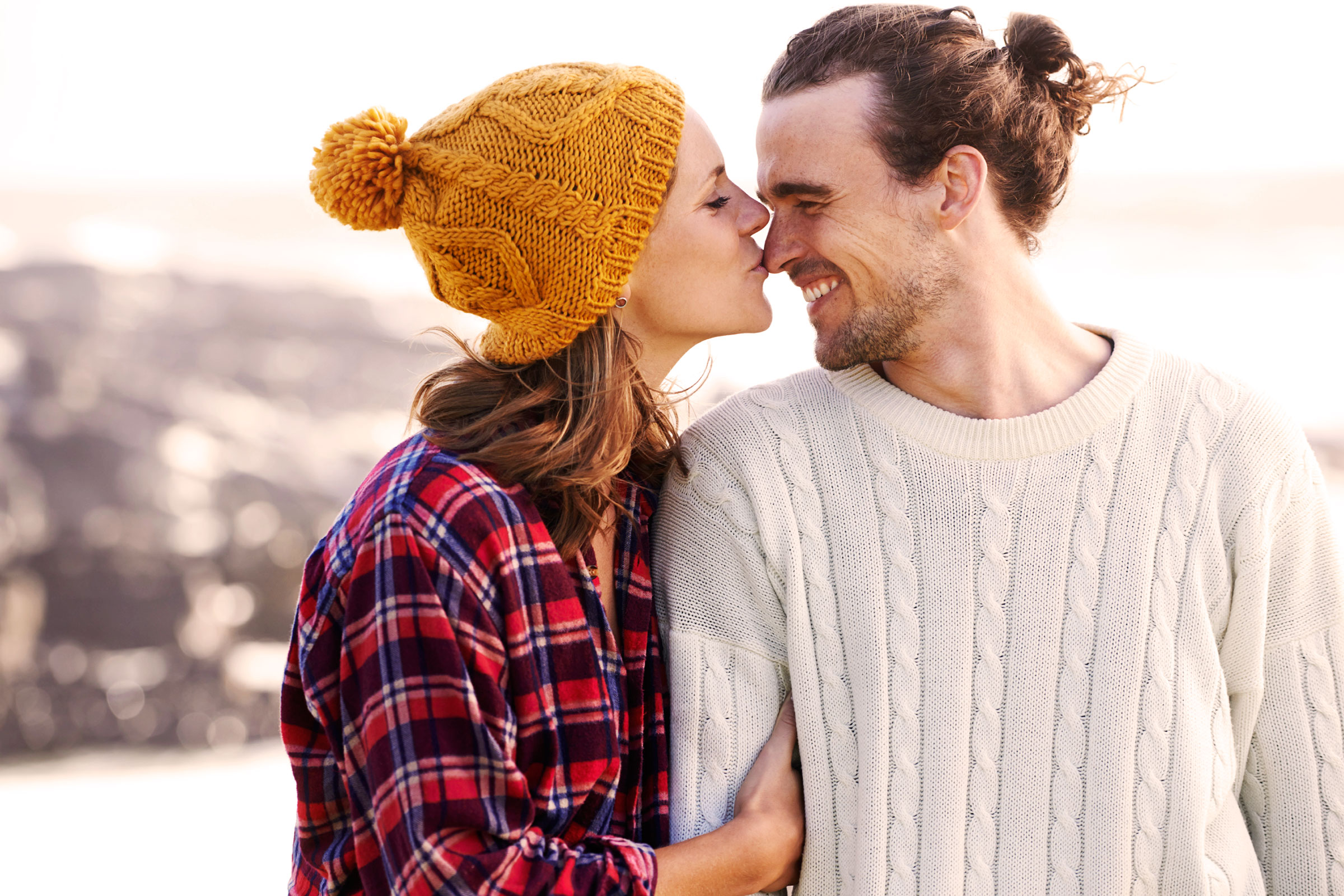 a couple kissing on a hike with a woman in plaid flannel and a man in a cable-knit sweather with a man bun.