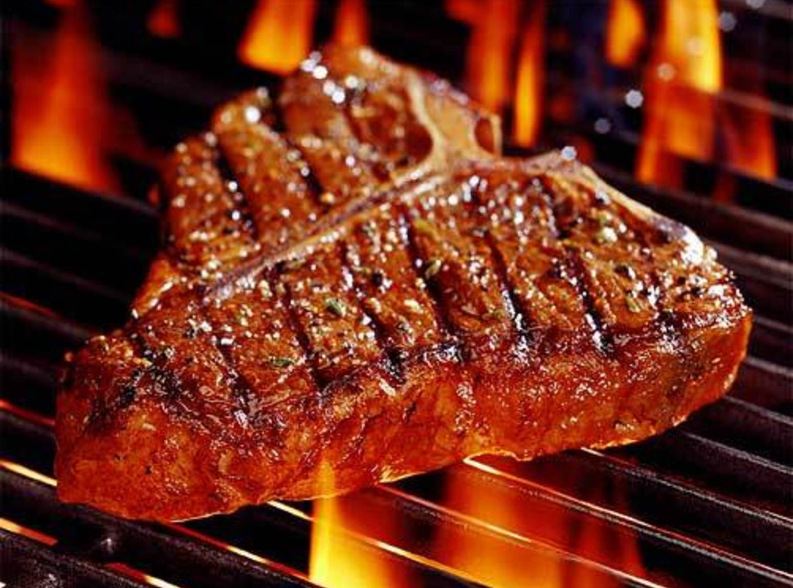 flame-kissed t-bone steak on an open grill