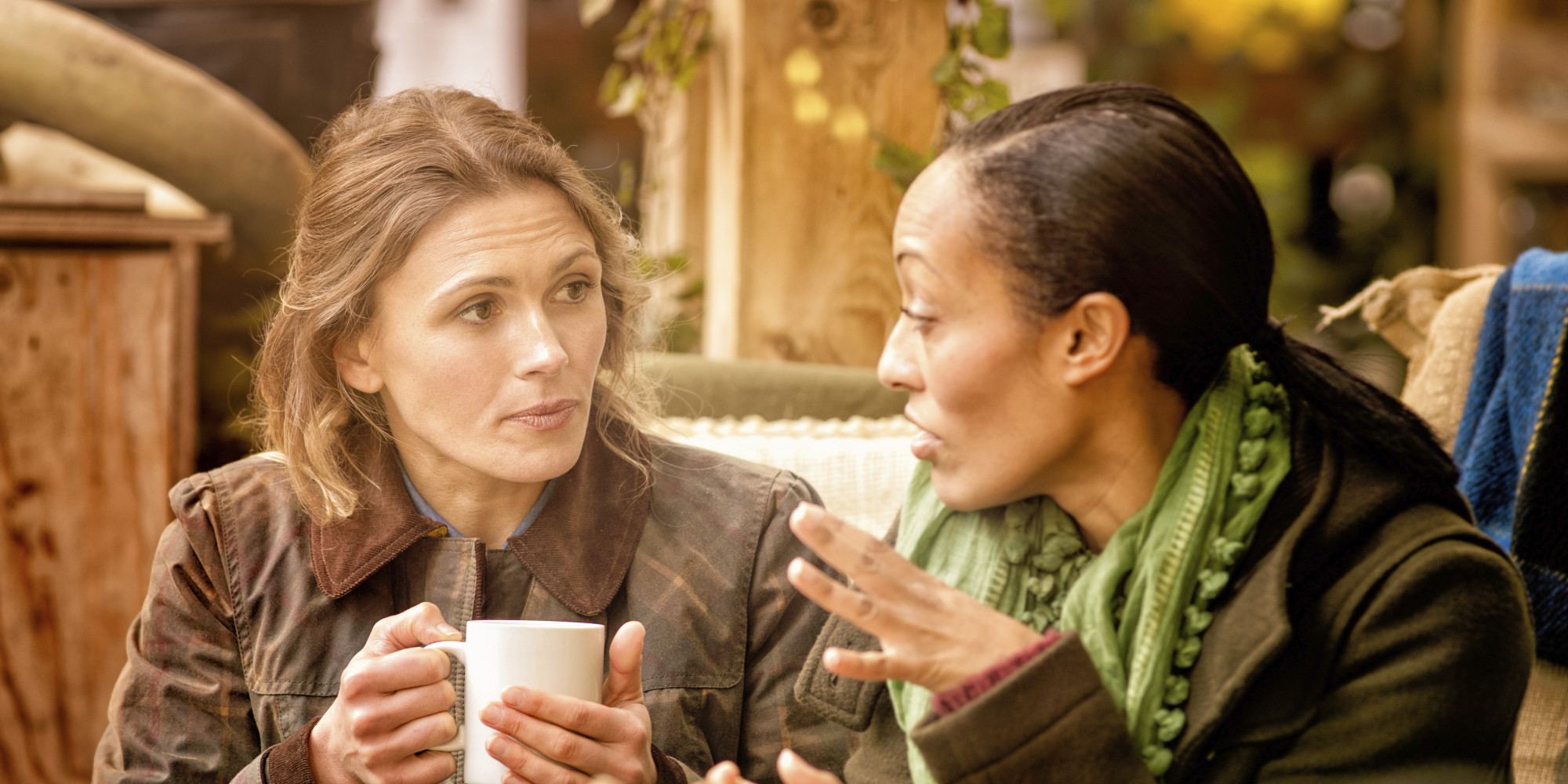 Two women talking or chatting over coffee, one is white and one is black.