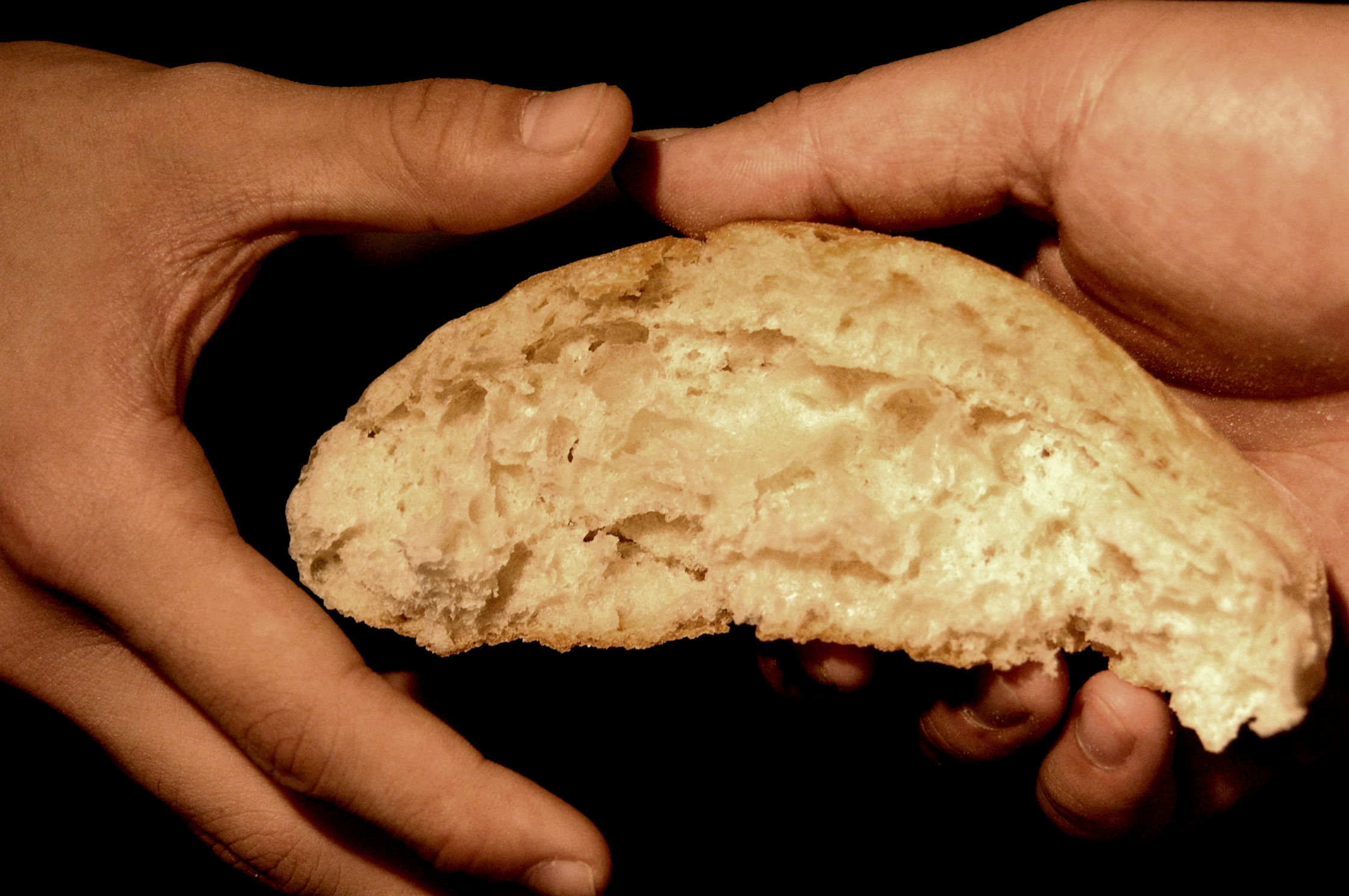 bread being passed from one person to another, just as Jesus fed the 5,000 in John 6