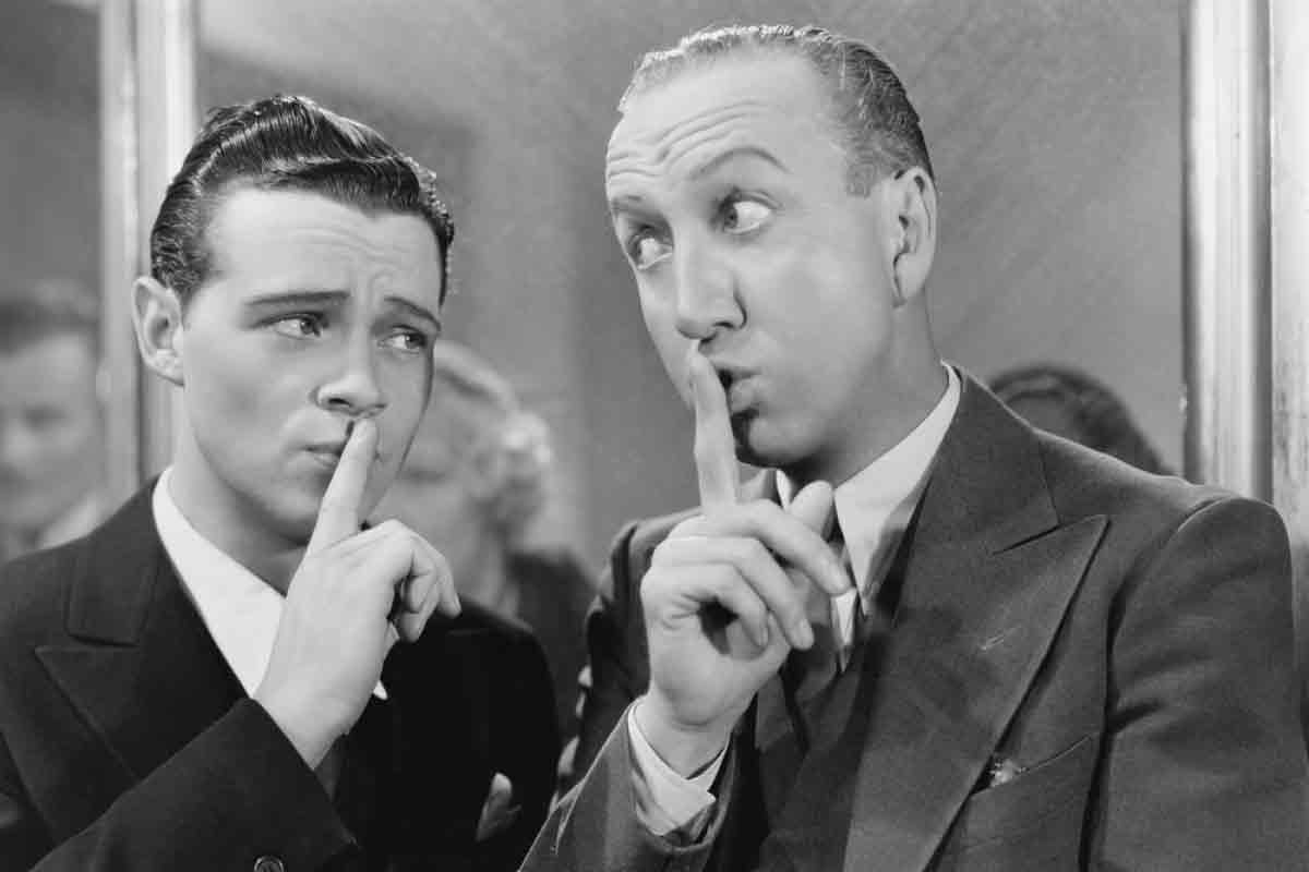 two men putting fingers over the mouths to indicate silence or a silent moment.