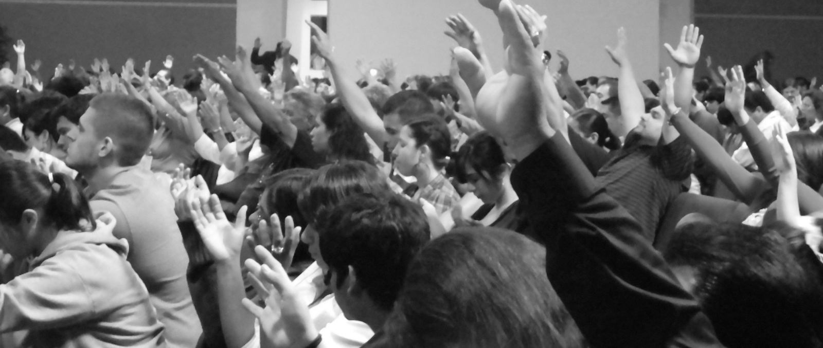 young people raising hands in revival in repentance and worship to God.