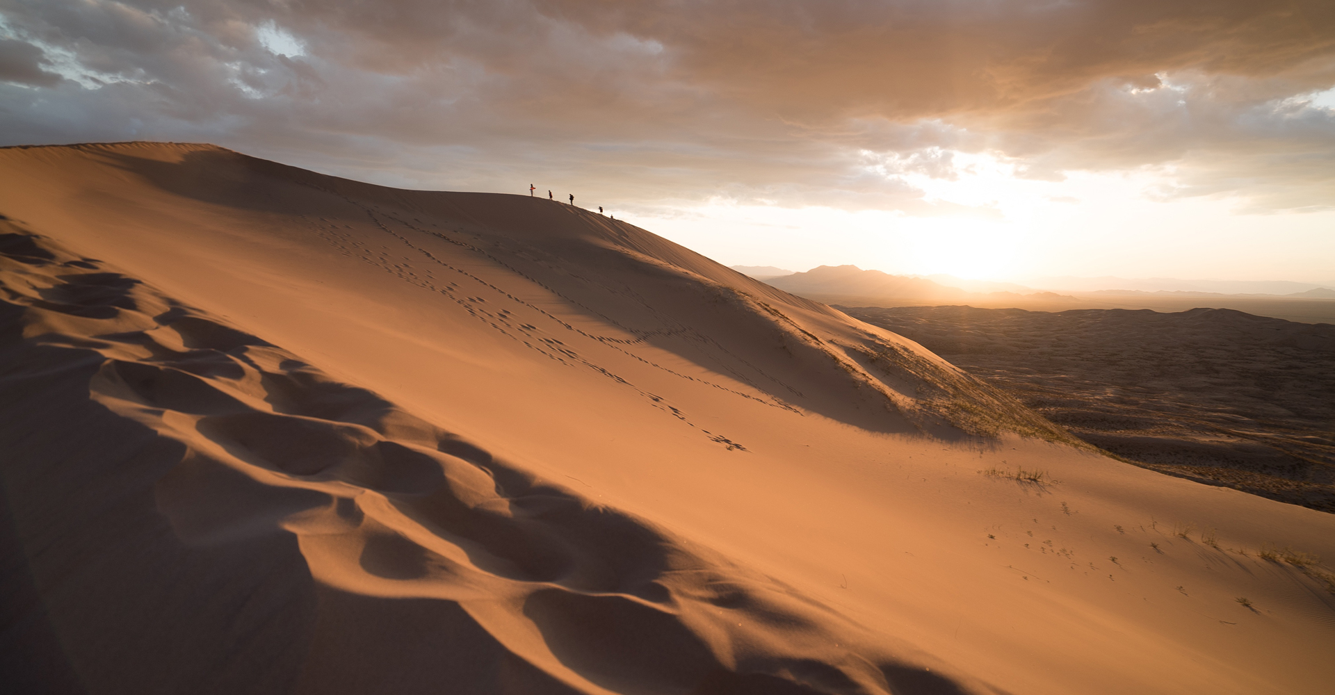 a vast desert landscape at twilight with only a few travelers and their tracks
