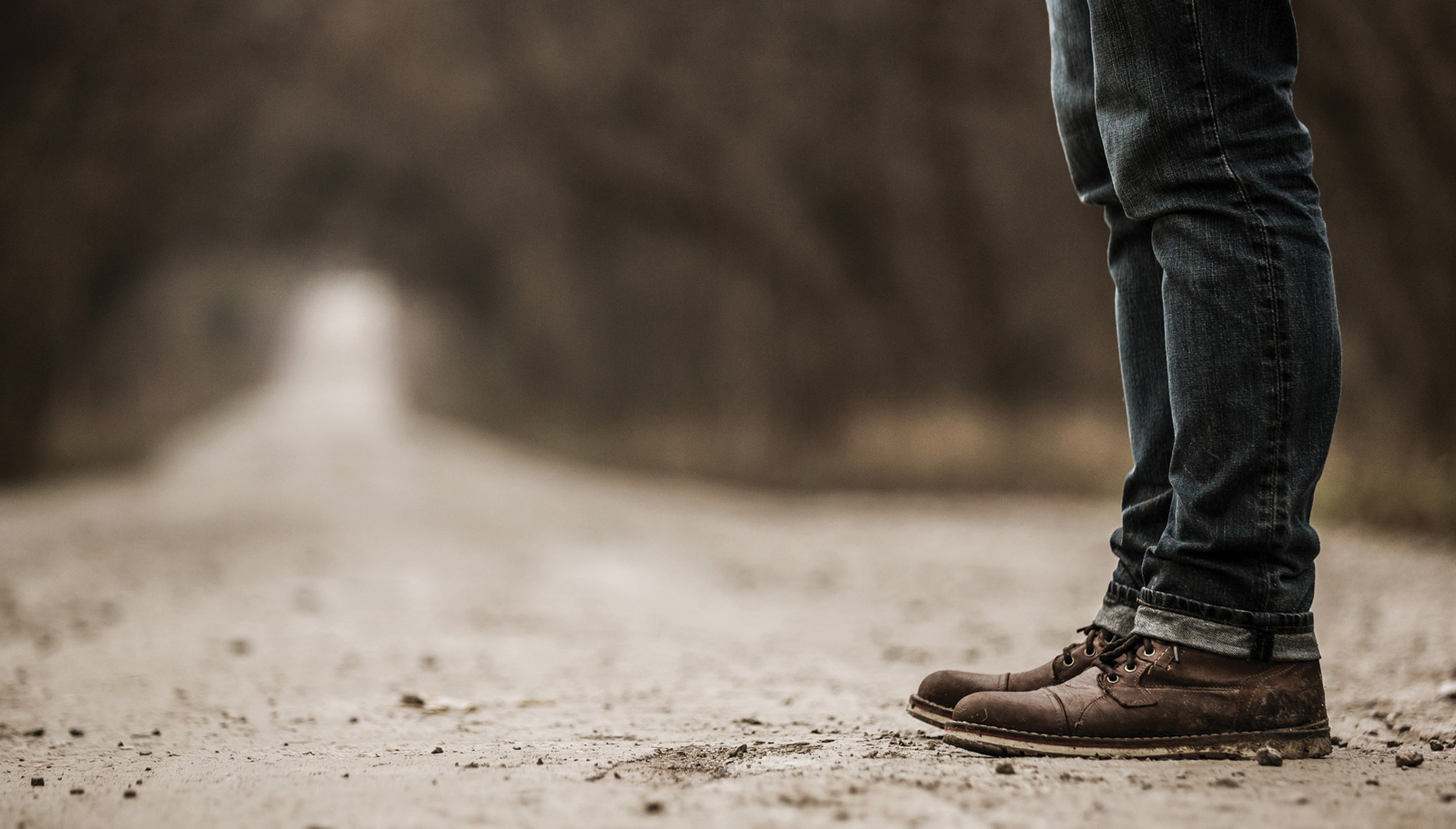 Man with brown boots standing at a crossroads, deciding whether to repent of not deal with repentance.