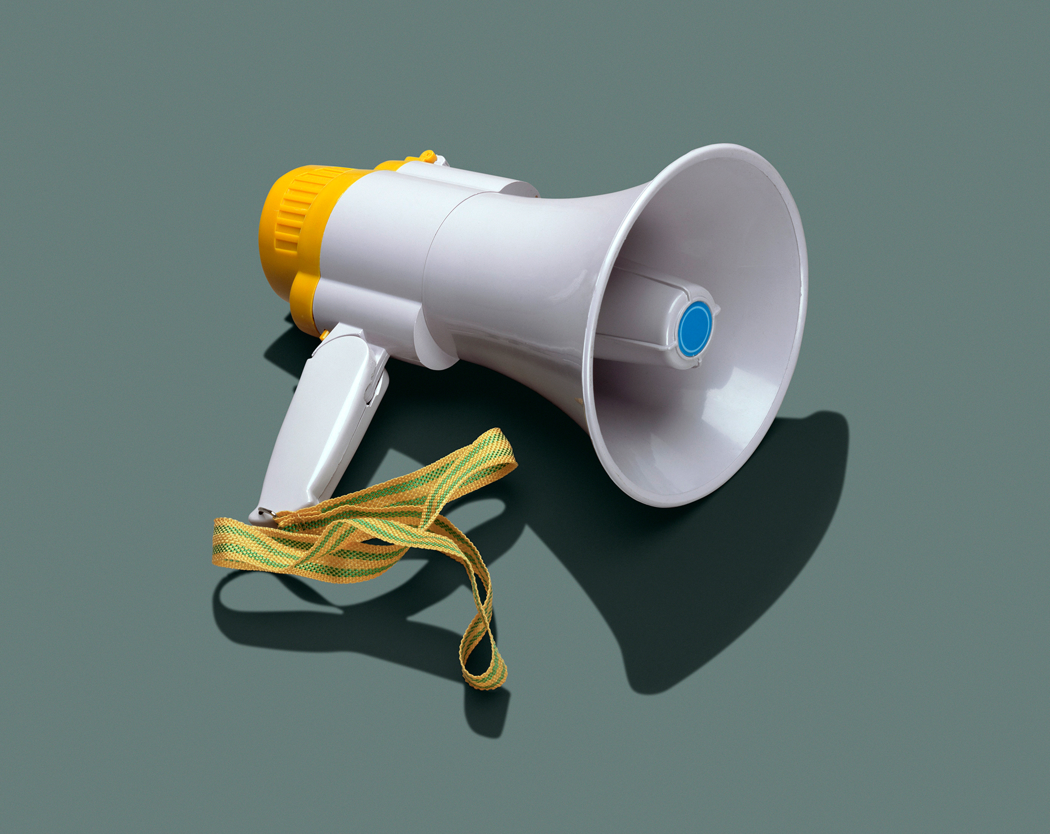 white megaphone with a yellow and green wristlet against a great-green background and shadow underneath.