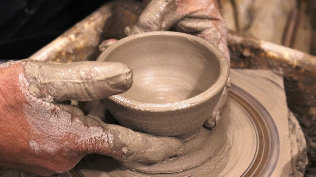 older, messy hands shaping (or throwing) a cup or small bowl on the pottery wheel