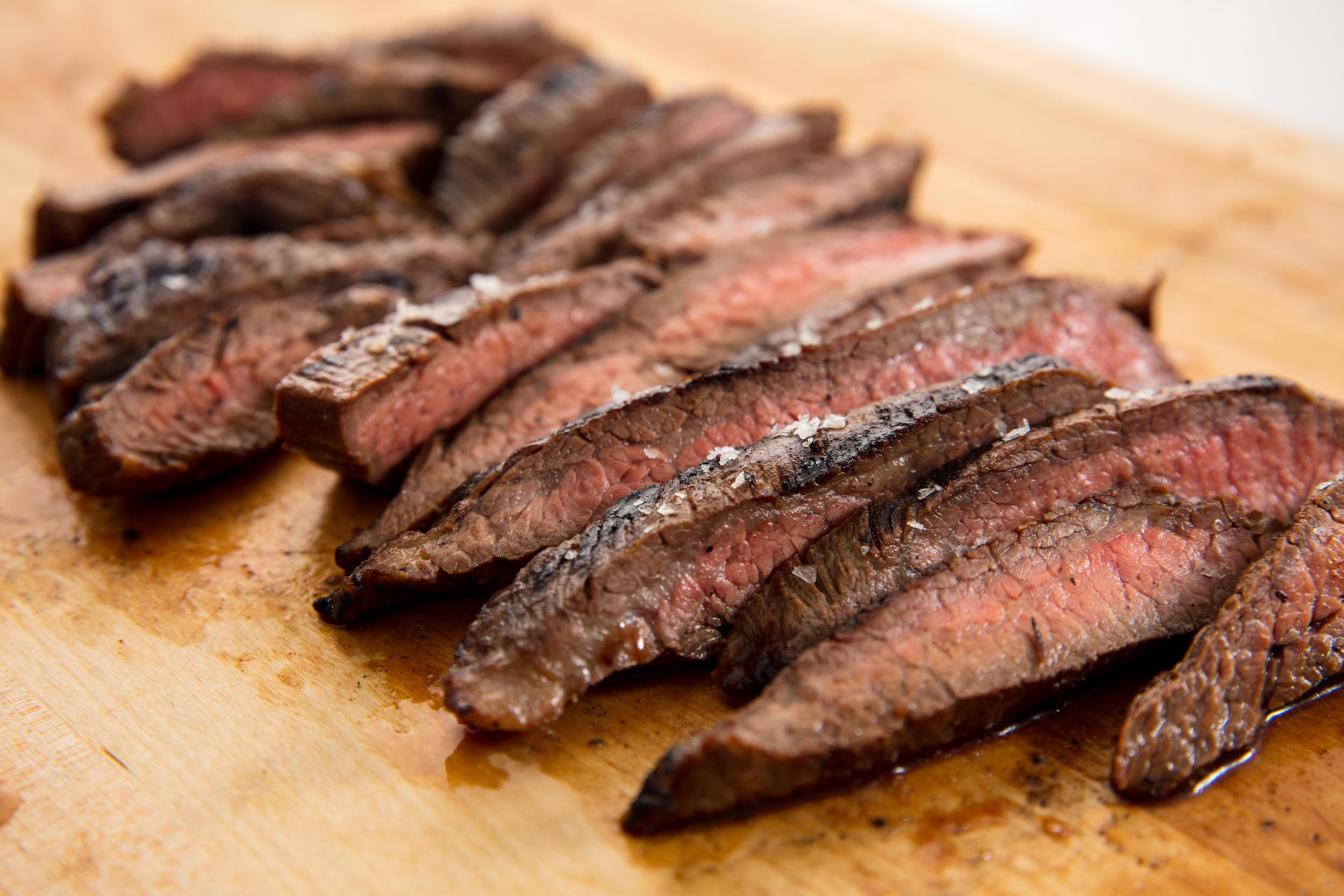 marinated flank steak laid horizontally on a cutting board and ready to be served at a party.
