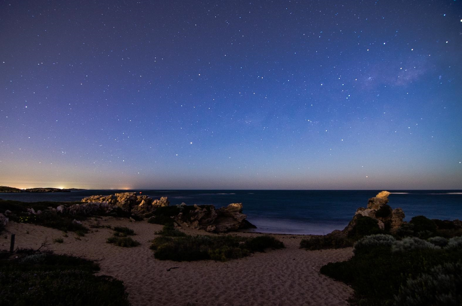 a beach at twilight or dawn where you can count the stars in the sky