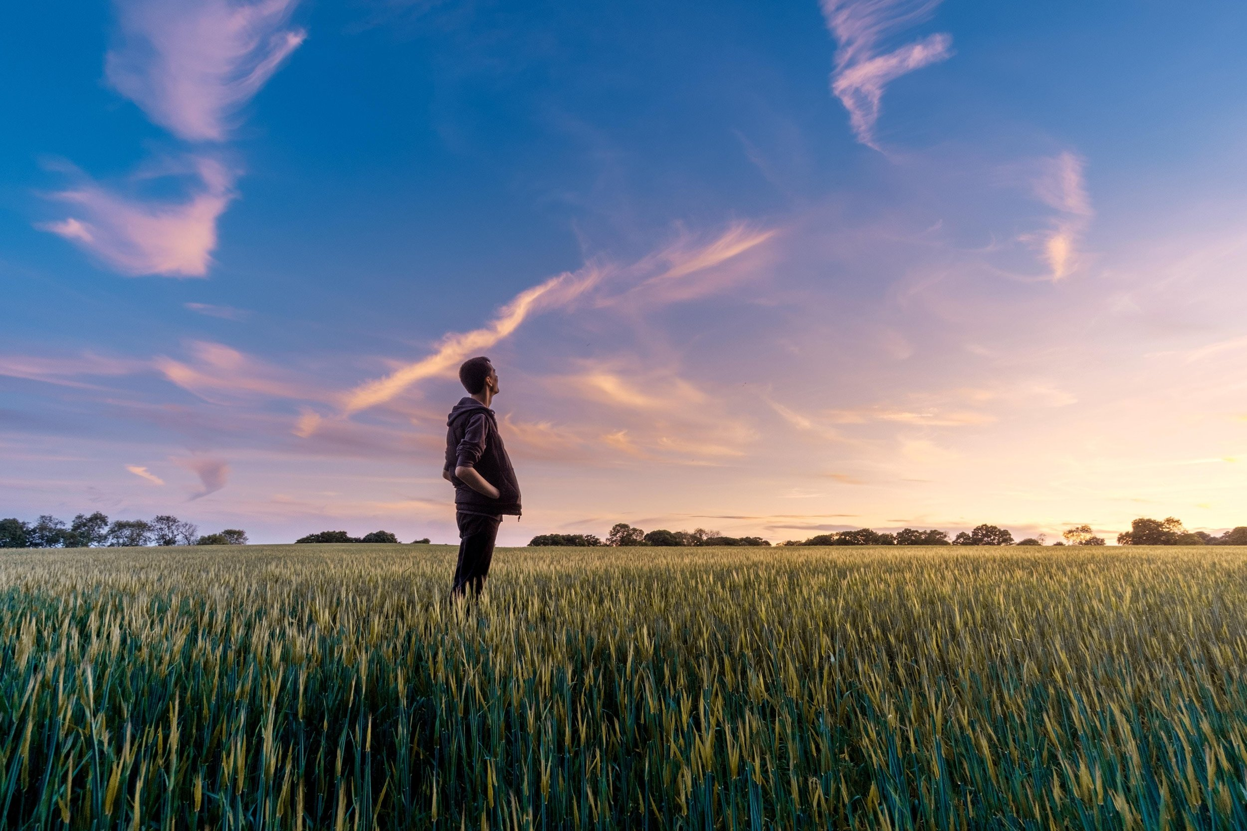 young man in a hoodie in a field looking wistfully into the breaking dawn, and dreaming of the future