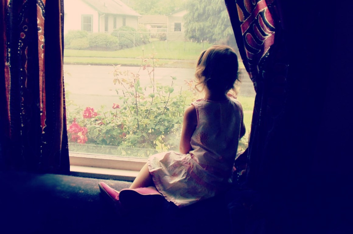 a little girl sitting by the window sill, waiting for someone to return home as a symbol of waiting for Jesus during the Advent season.