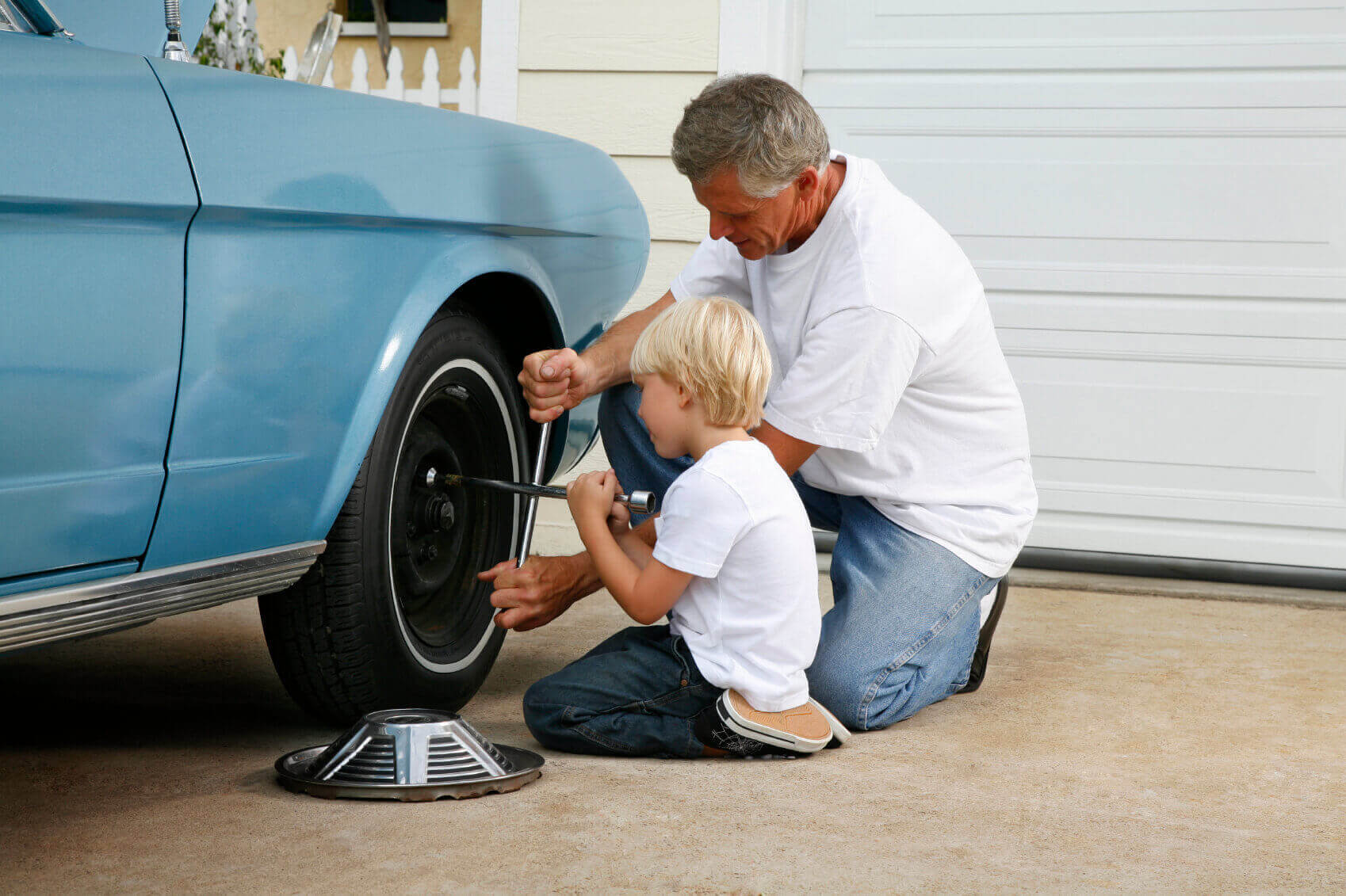 Father and son working on a car together changing a tire