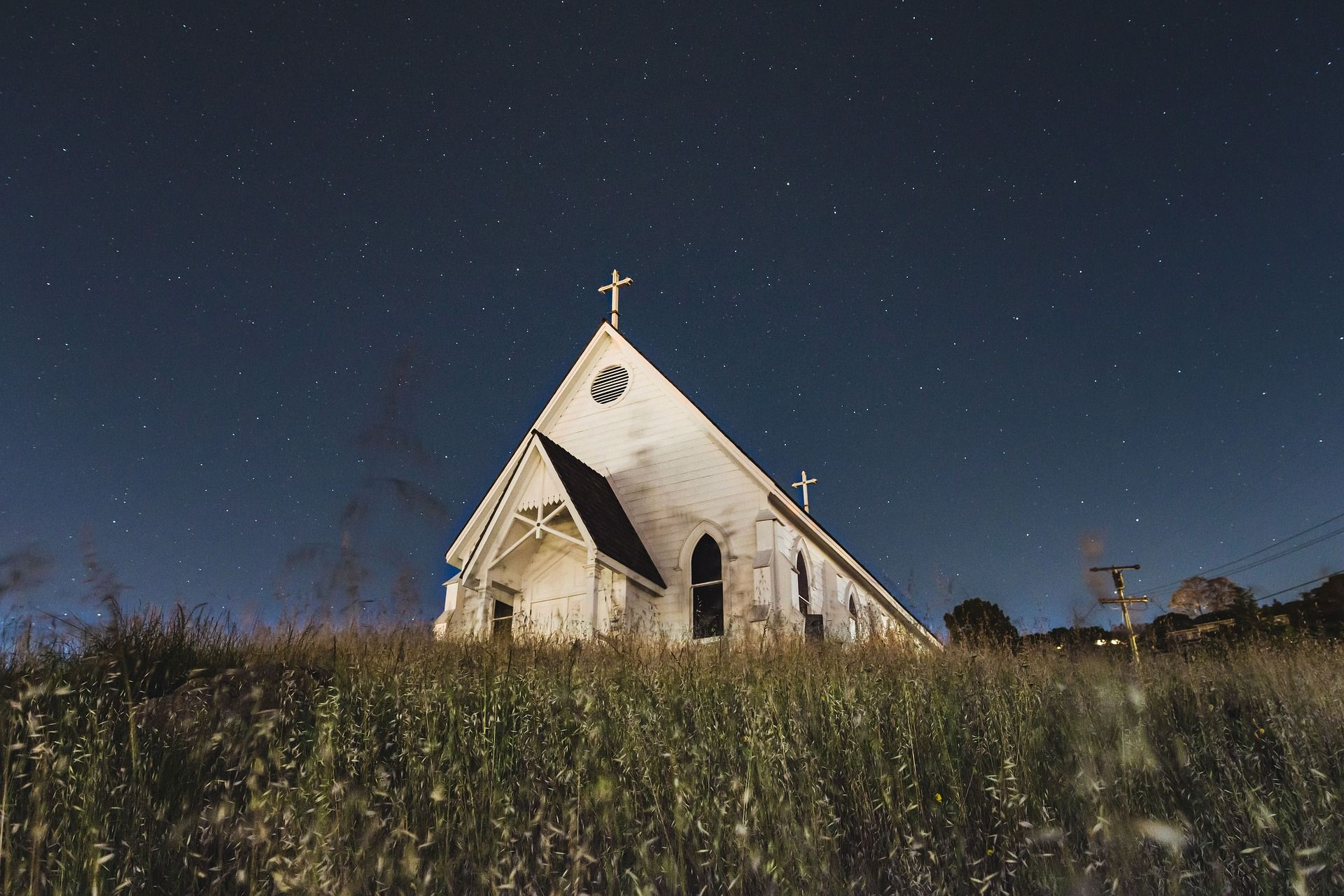 A lone white church appearing to be standing on its own in a grassy field.