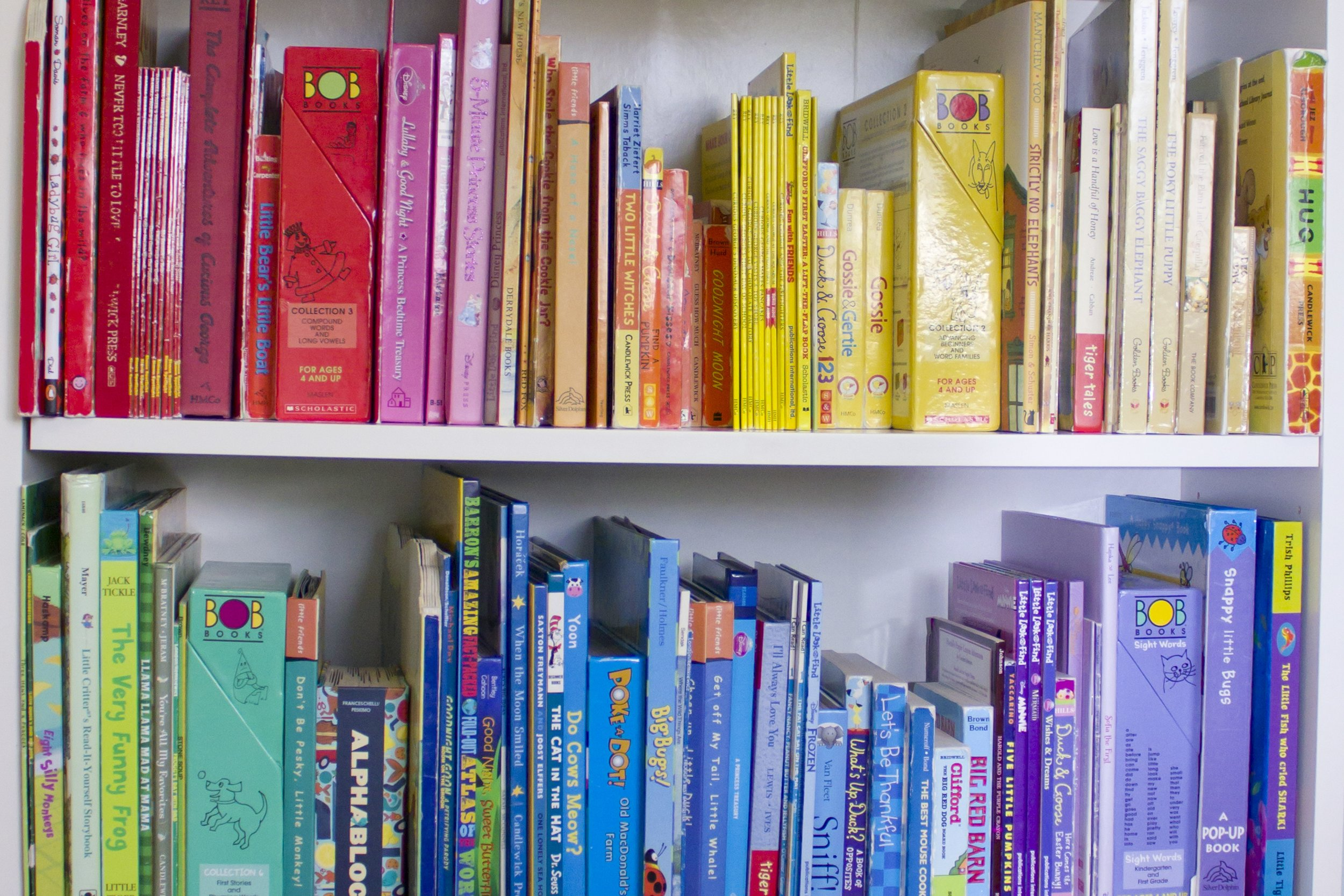 books ordered by colors of the rainbow on a white bookshelf with a close-up