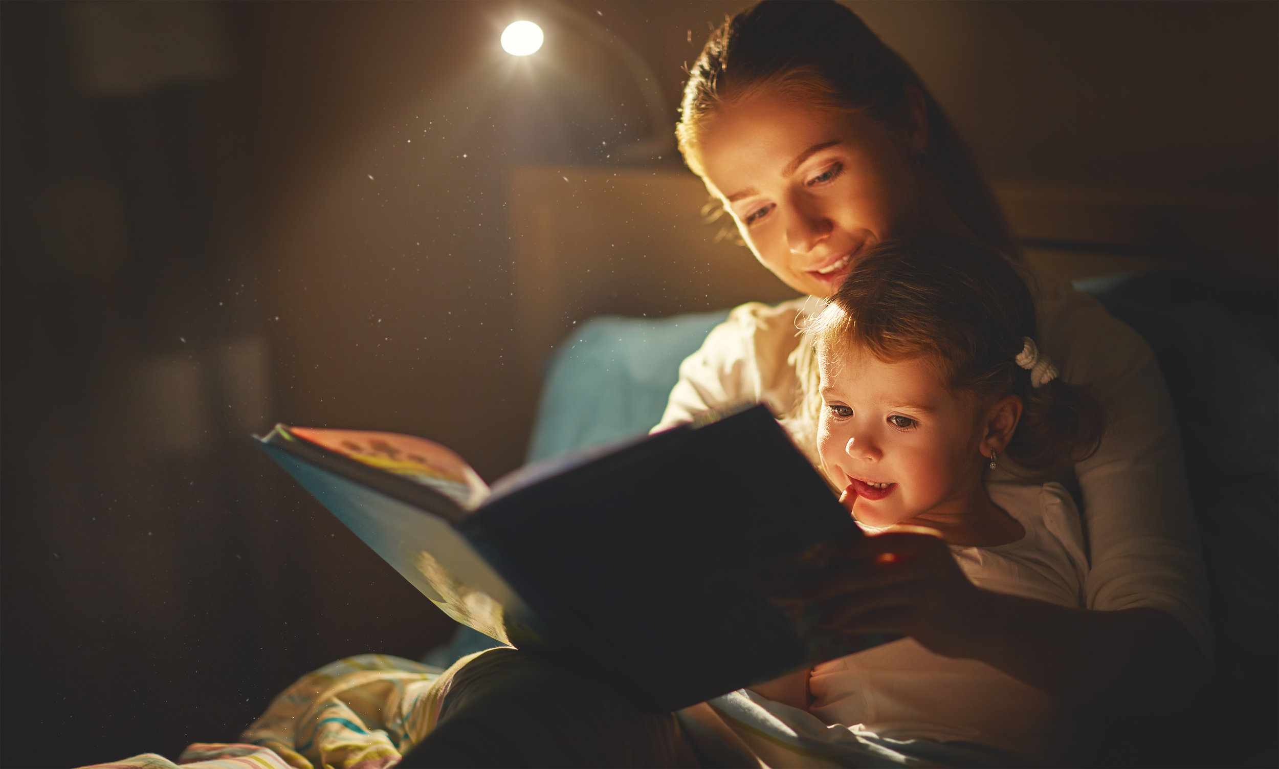 a mother and daughter reading a book together for a bedtime story session in bed