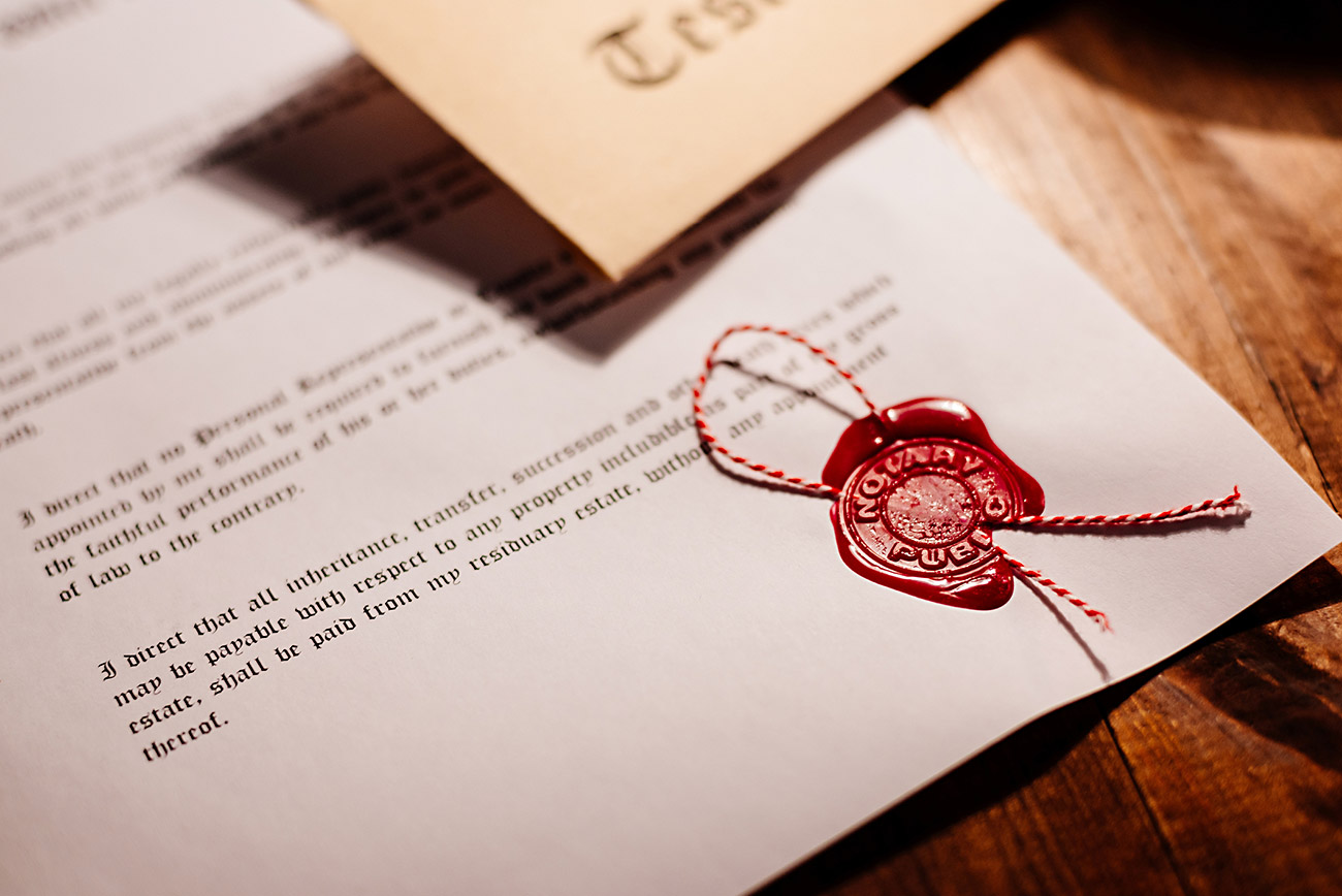 Last will and testament marked with a seal of authenticity, laying on a wooden table
