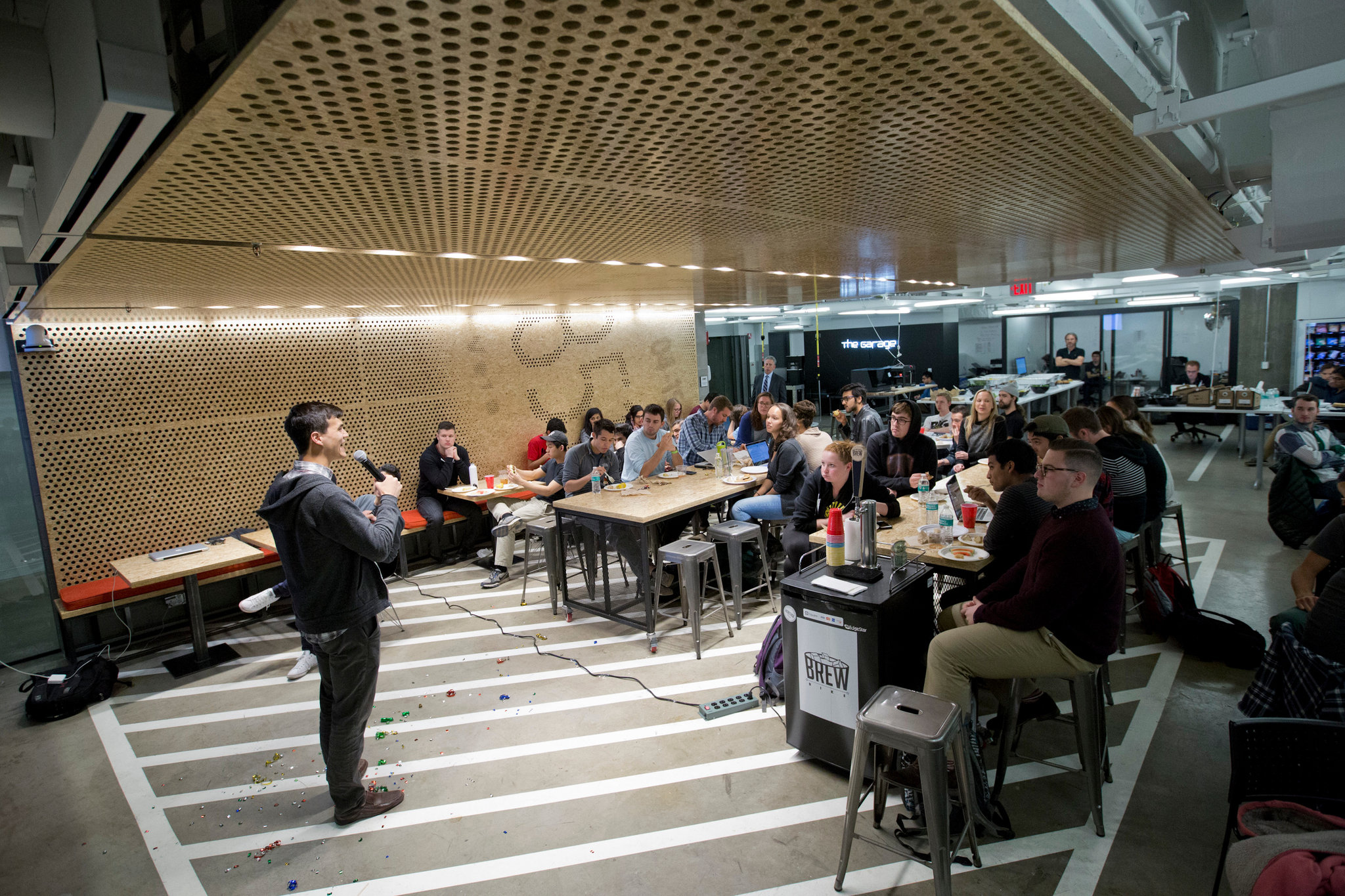 Griffen Kelly, a founder of Trac and a Northwestern alumnus, speaks to students during the weekly dinner at the Garage, which was built in one. Note the parking lines on the floor.CreditNathan Weber for The New York Times