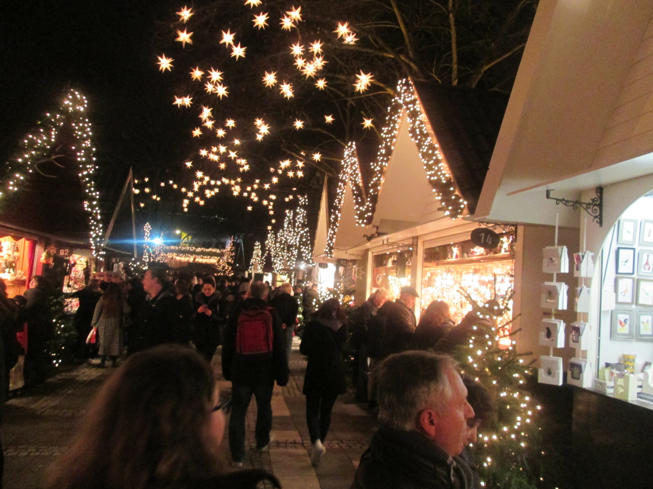 Stands in the Weihnachtsmarkt at Neumarkt in Köln with illuminated stars hung from trees overhead