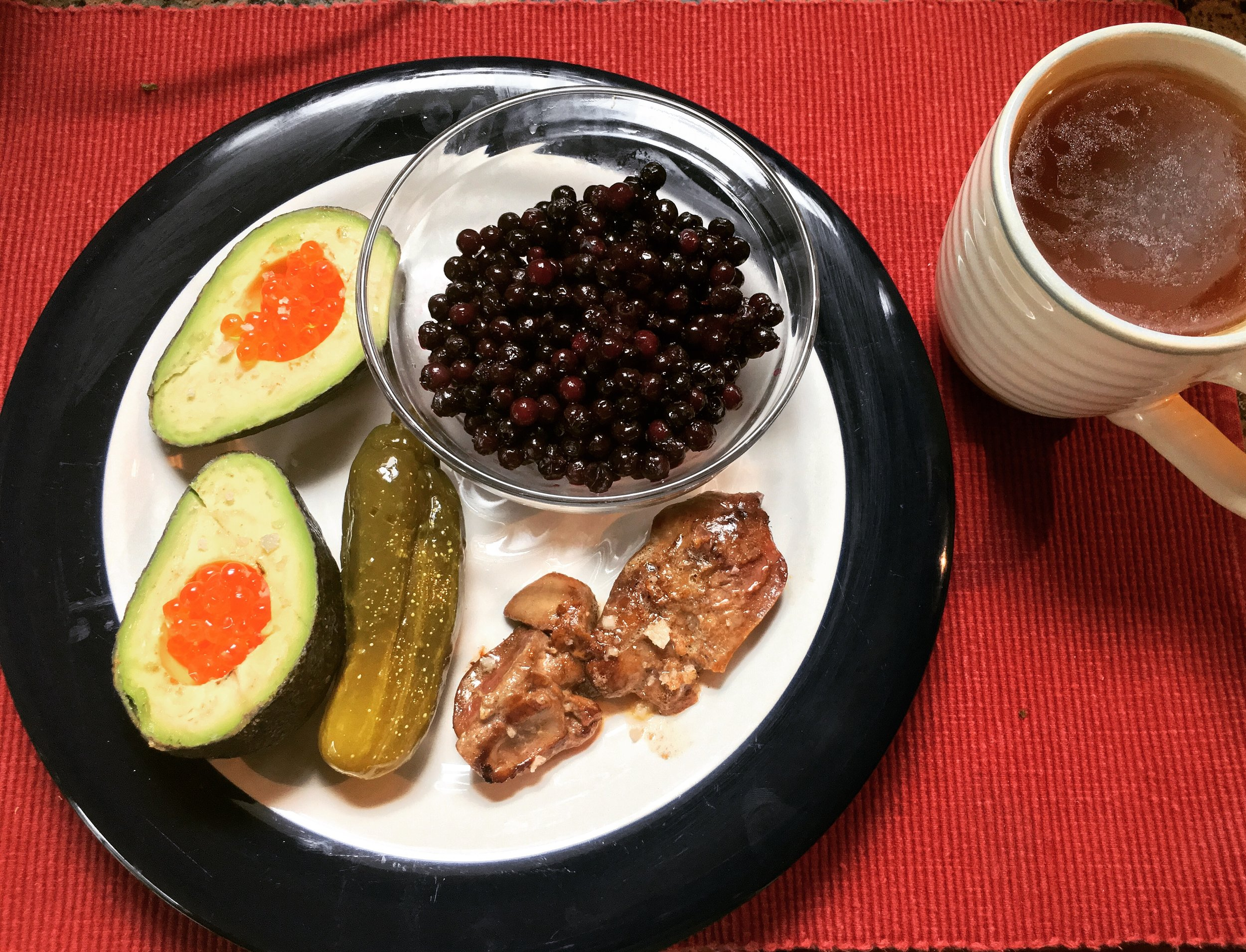 This is an example of a highly nutrient-dense breakfast:  Chicken liver seared in grass-fed butter with truffle sea salt, fermented pickle (probiotic), whole avocado with caviar/salmon roe, organic blueberries and homemade broth.