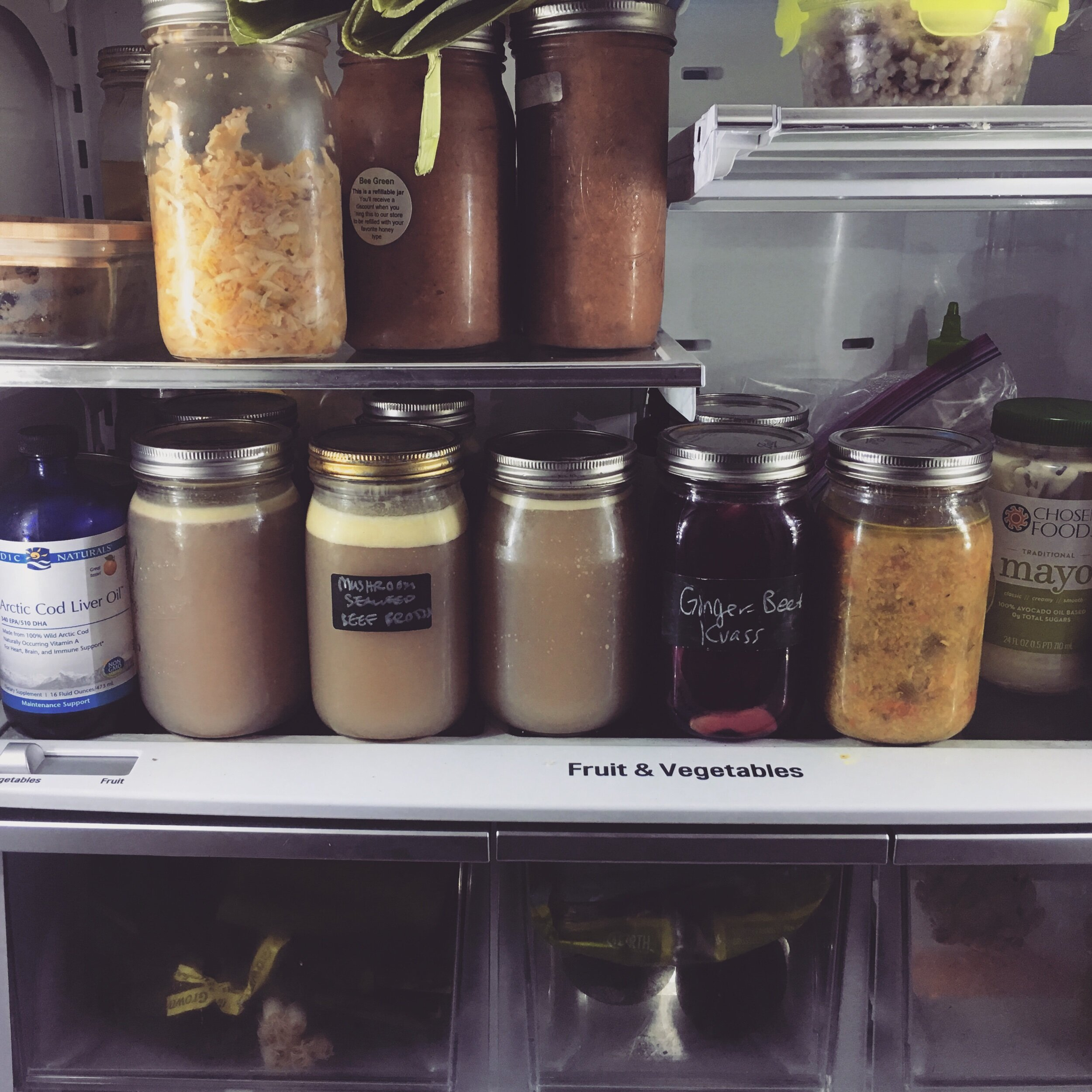 A current snapshot of my fridge, Contents in case you're interested (from top left): baked sweet potato, apple parsnip kraut, apple-quince sauce, leftover buckwheat, cod liver oil, bone marrow and oxtail pho broth, mushroom seaweed beef broth (from second batch), ginger beet kvass, leftover chicken soup, avocado oil mayo.