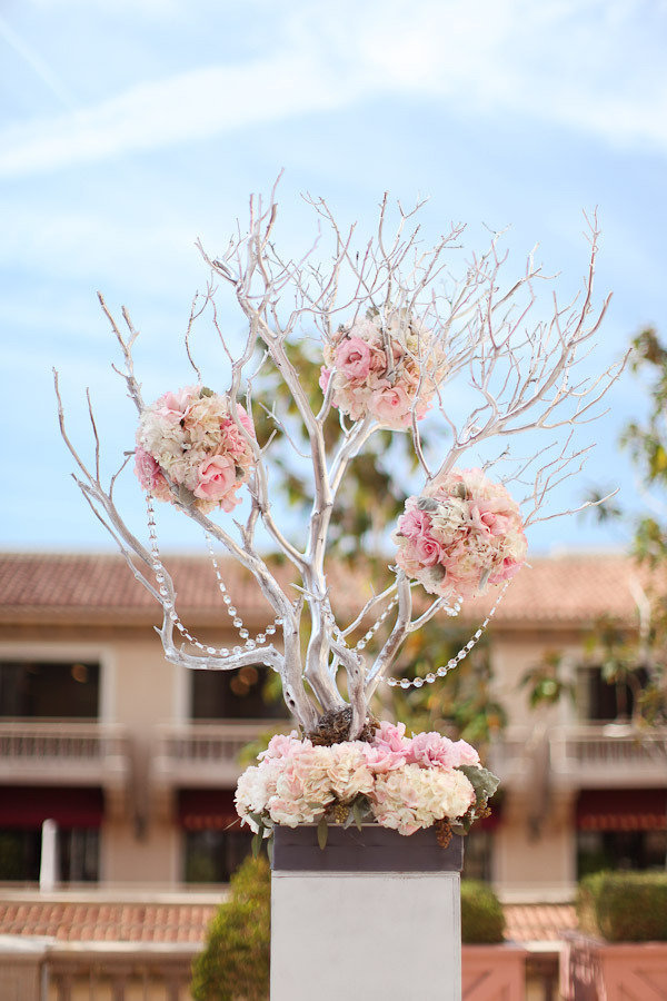 Wedding decor featuring a sliver-painted manzanita tree and fresh flowers.