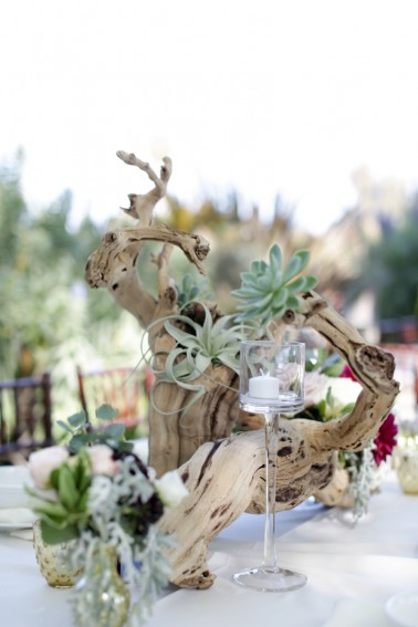 An ocean side wedding's grapevine centerpieces get a dash of green thanks to strategically placed succulents.