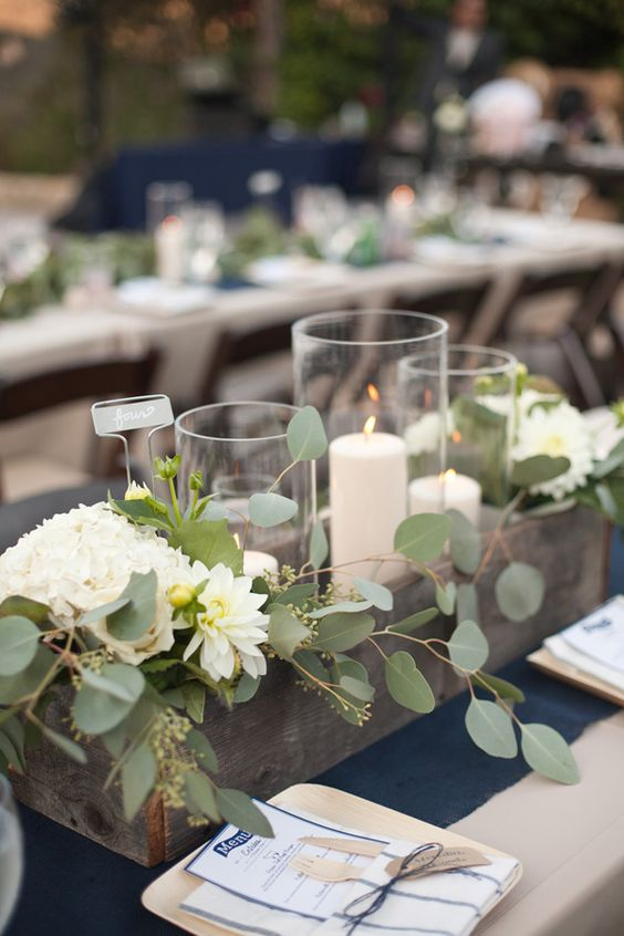 A lovely eucalyptus and candle centerpiece arranged in a long wooden box is a great example to follow for long, rectangular tables.