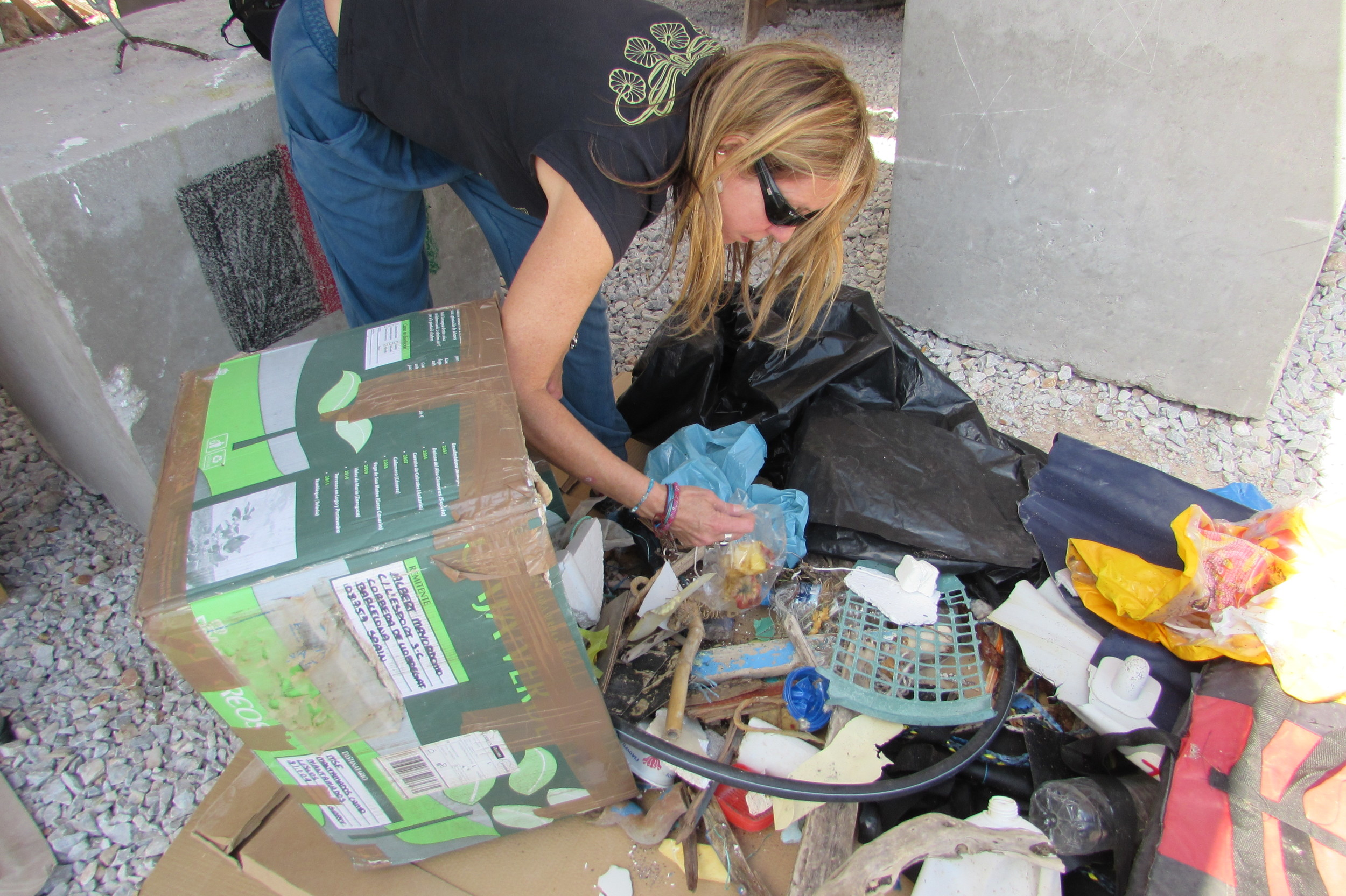 PPC Artist Ally Pam Longobardi sifts through waste materials collected by refugees on Lesbos.