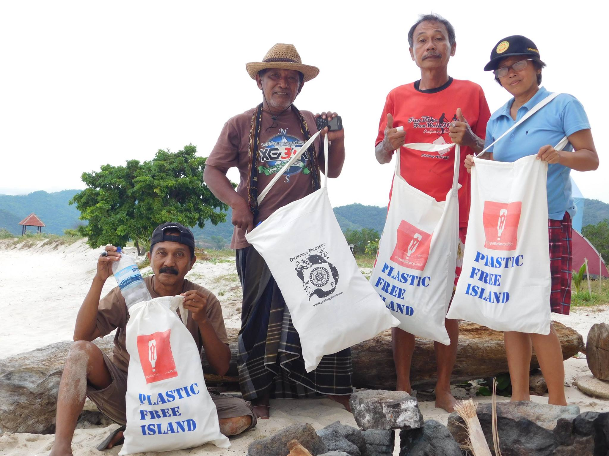 Local   naturalist Amiruddin Using (second from left) shows reusable cotton bags for collecting plastic.