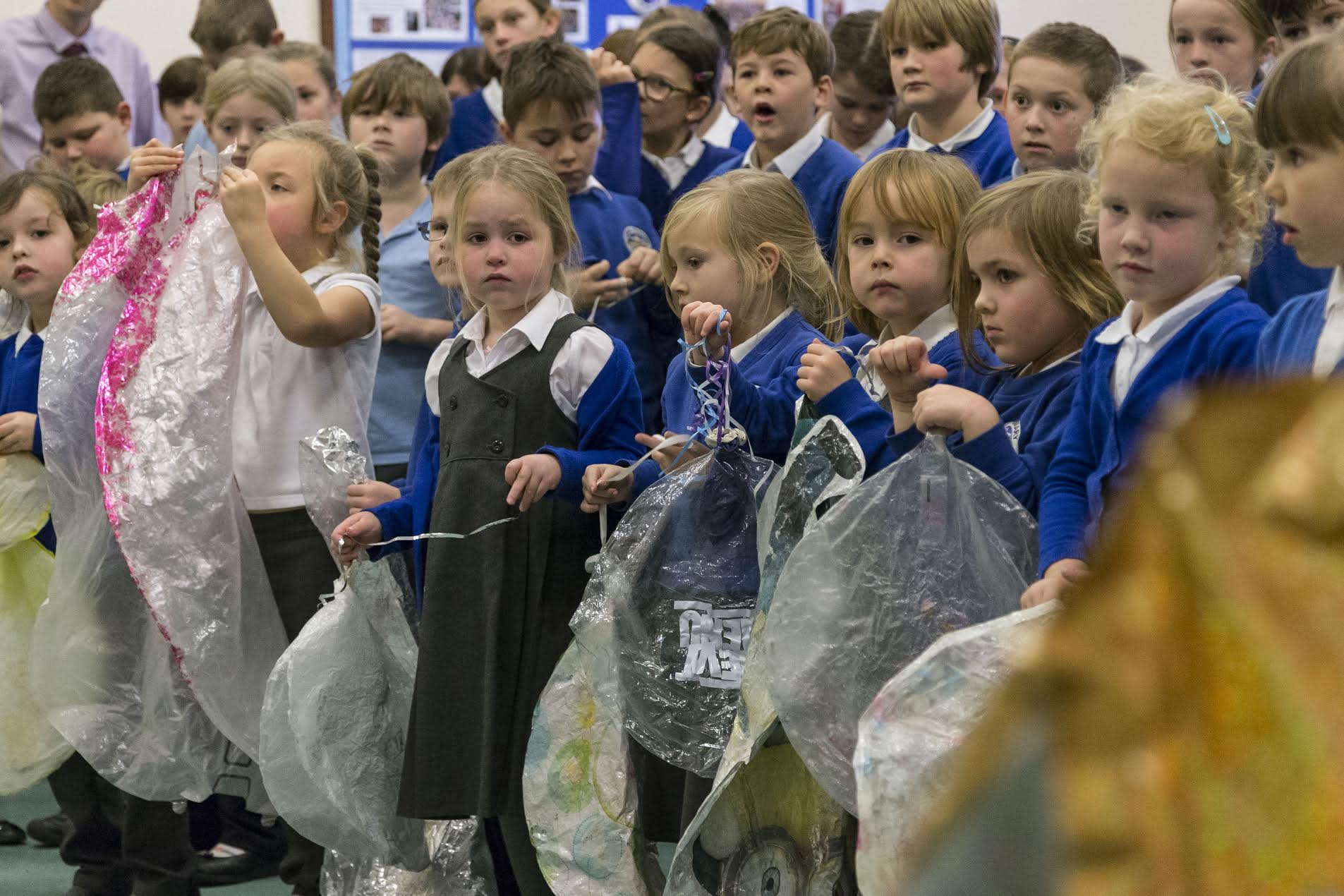 Children in Cornwall, England, hold up ninety-nine dead balloons that were collected on local beaches.