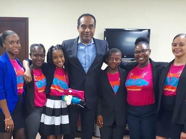 Youth from Bahamas Plastic Movement stand with the Minister