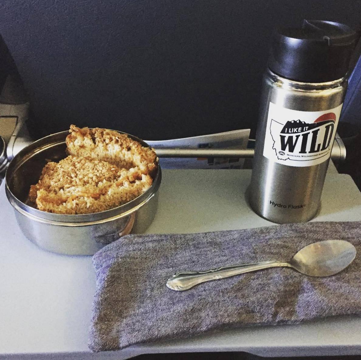 On a flight, Kara gets coffee in her reusable mug and brings her own snacks, utensils, and napkin.
