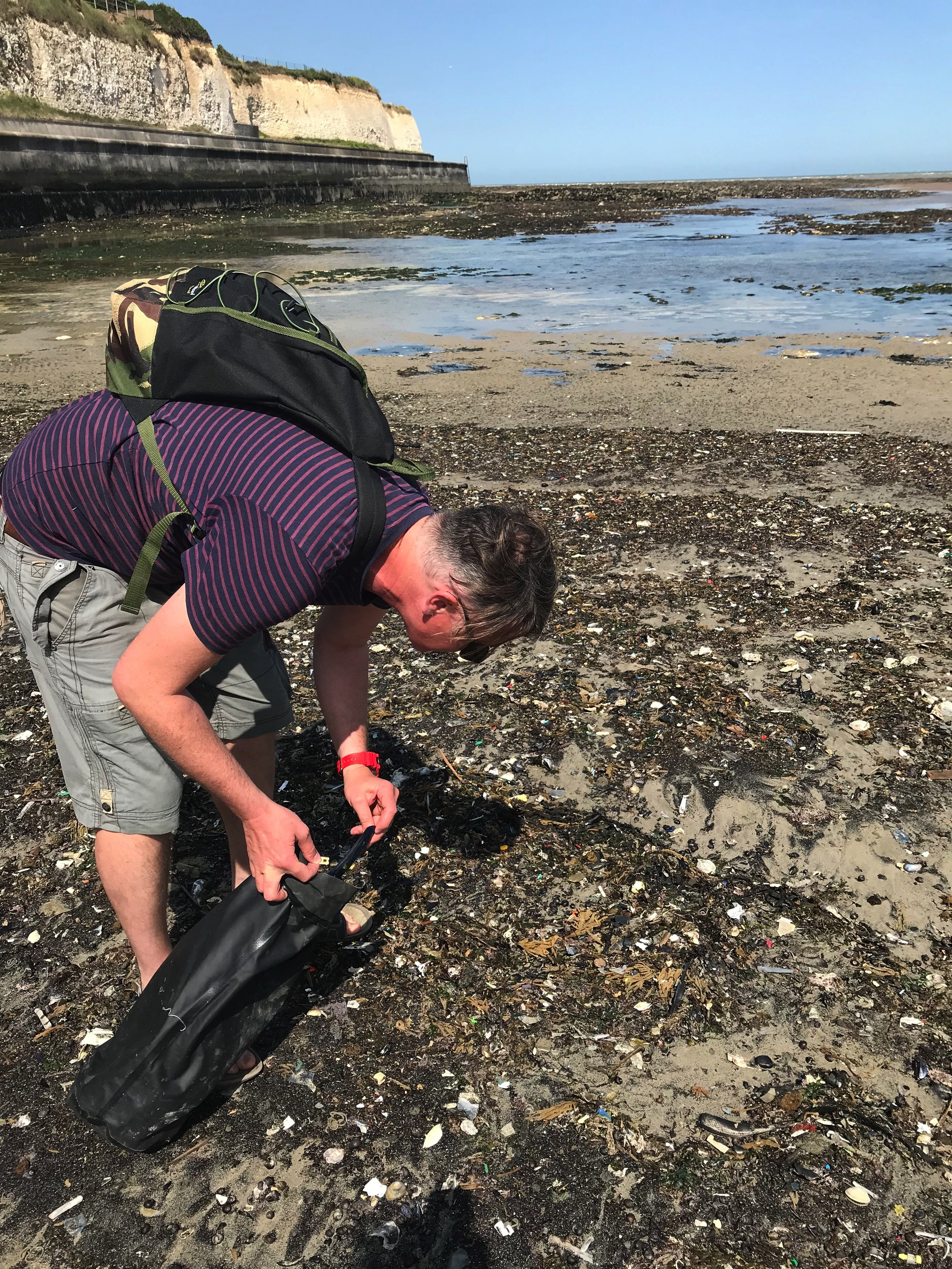 Artist at work: Steve McPherson collects plastic objects and fragments from the beach for future projects at Eccles Beach, Kent, UK.