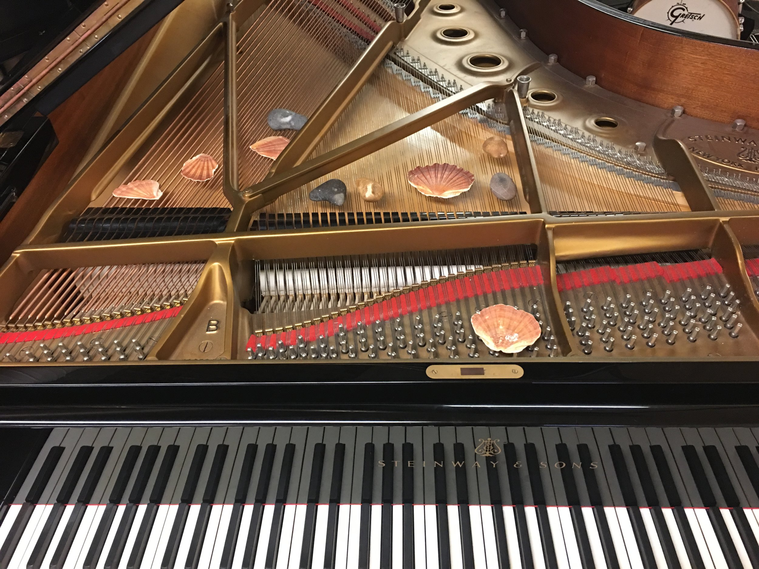 Rocks and shells placed on the strings inside the piano