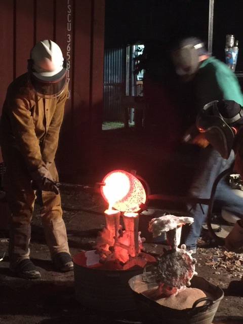 Carlos and Will lift the hot crucible of hot bronze out of the furnace and pour it into the shells. The one holding the pour end is called the dead men.