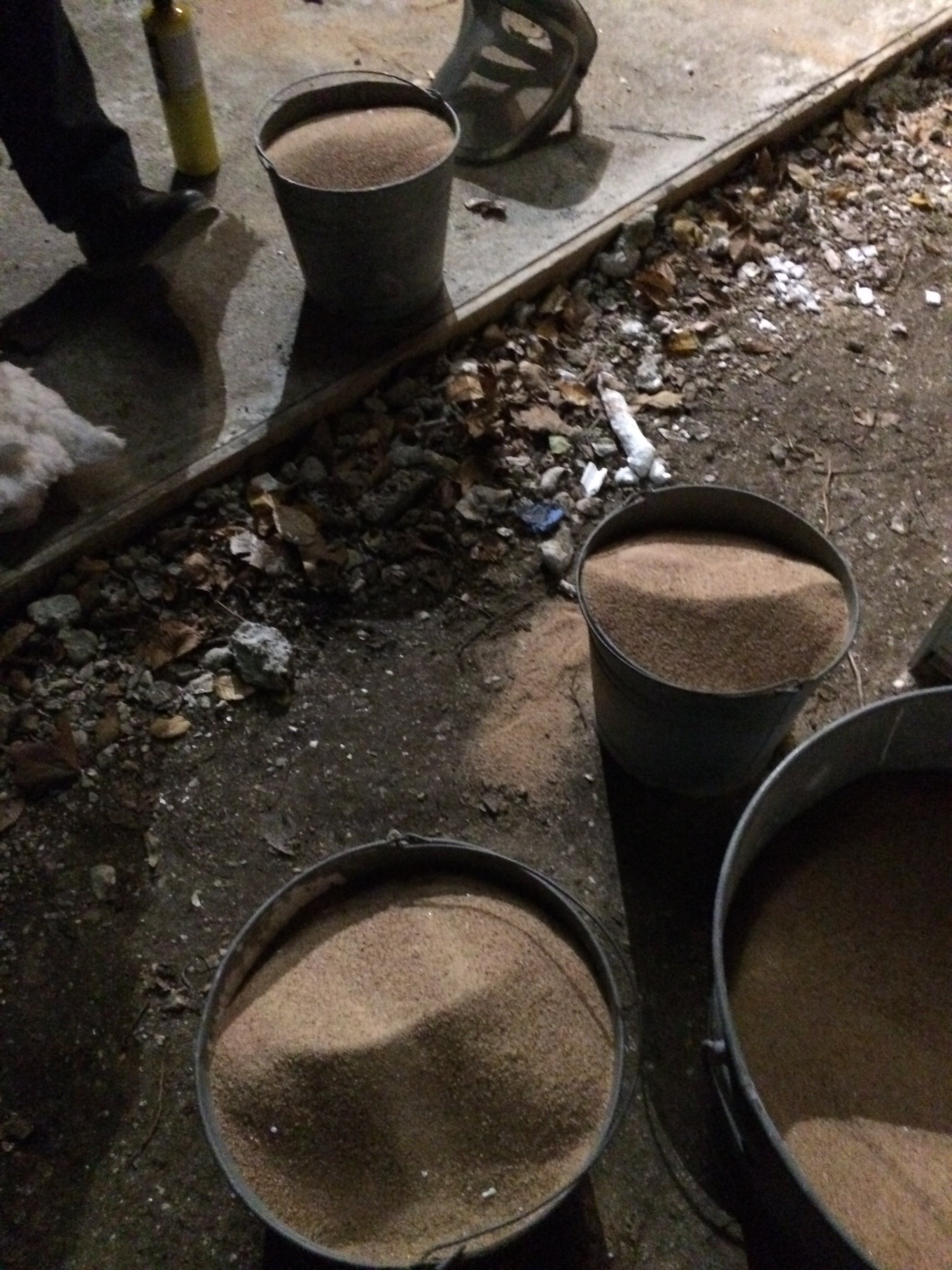 Buckets of sand ready to be poured around the shells.