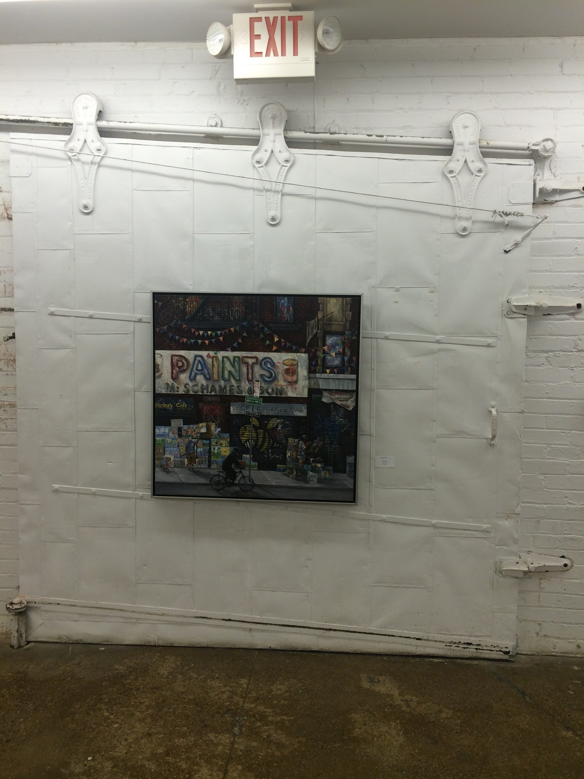 Industrial rolling doors used in the exhibit to hang a painting of a warehouse.