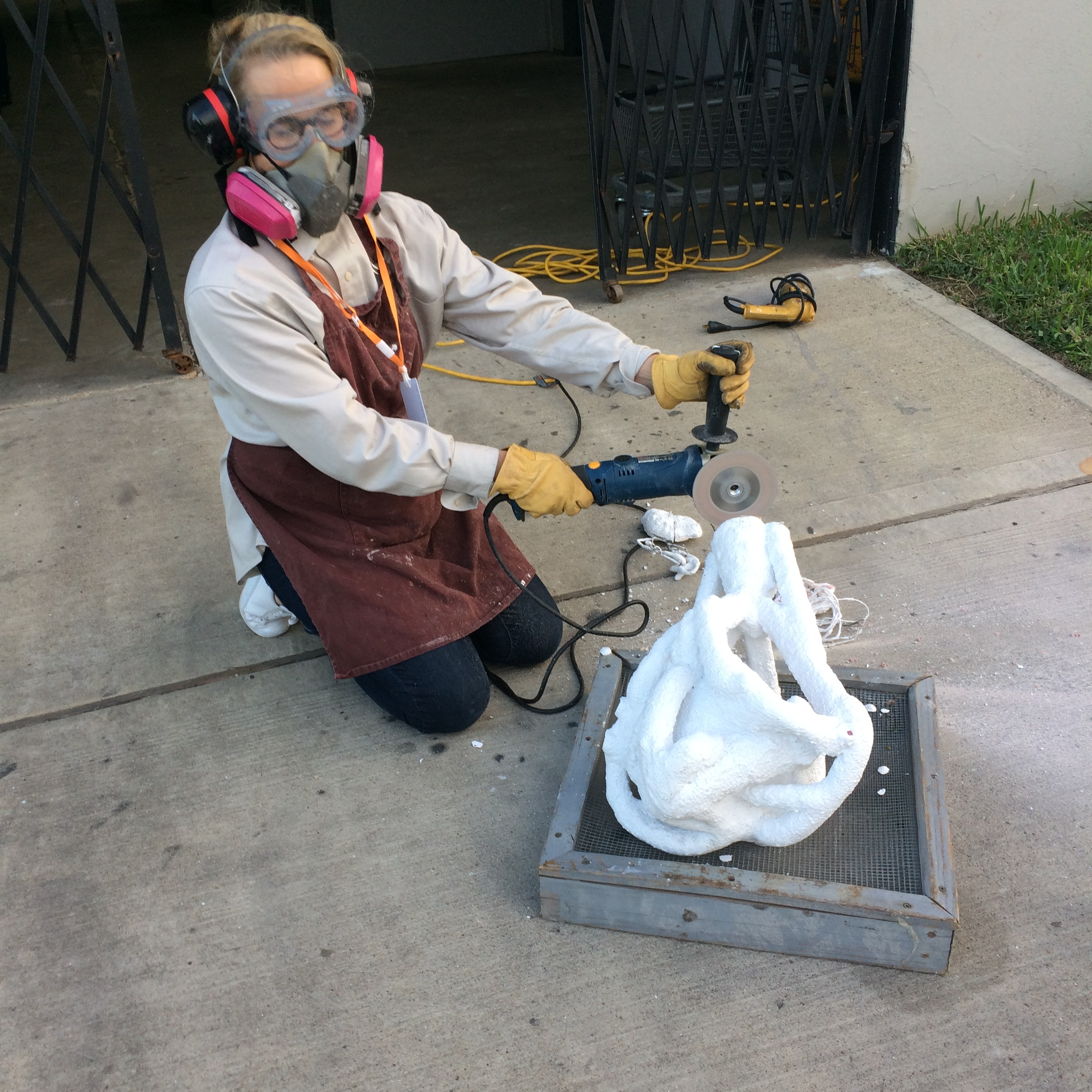 Here I am wearing ear and eye protection, a respirator and using my angle grinder with a diamond blade to cut off the top of the cup and blind vents.