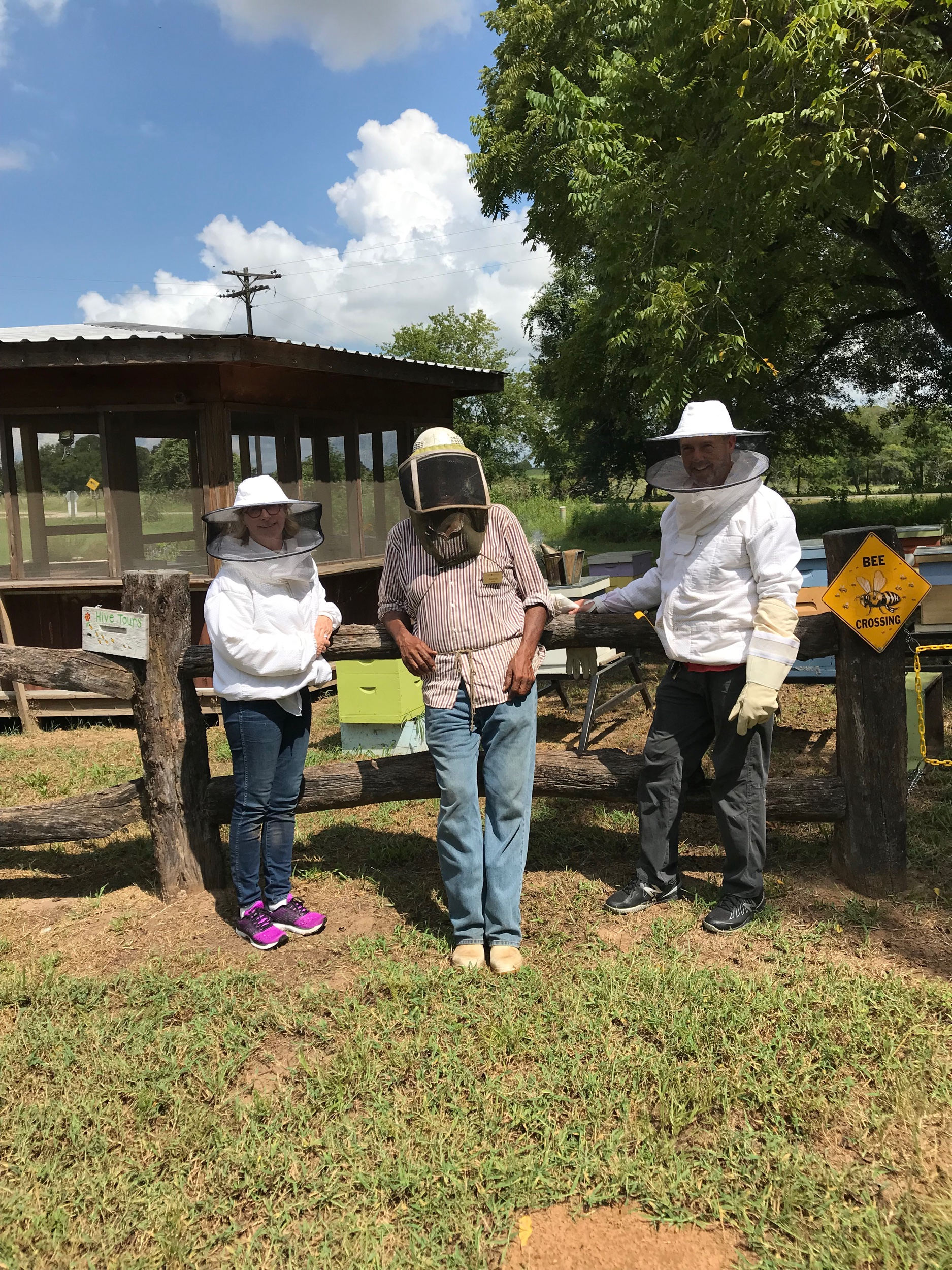 You need to wear long sleeves, loose jeans, and closed-toe shoes. They provide the bee nets/hats and jackets. We are posing in front of some bee boxes and trying to let you see the smoke can behind us. Roosevelt really wanted the smoke to show in the picture. You can't see the smoke.