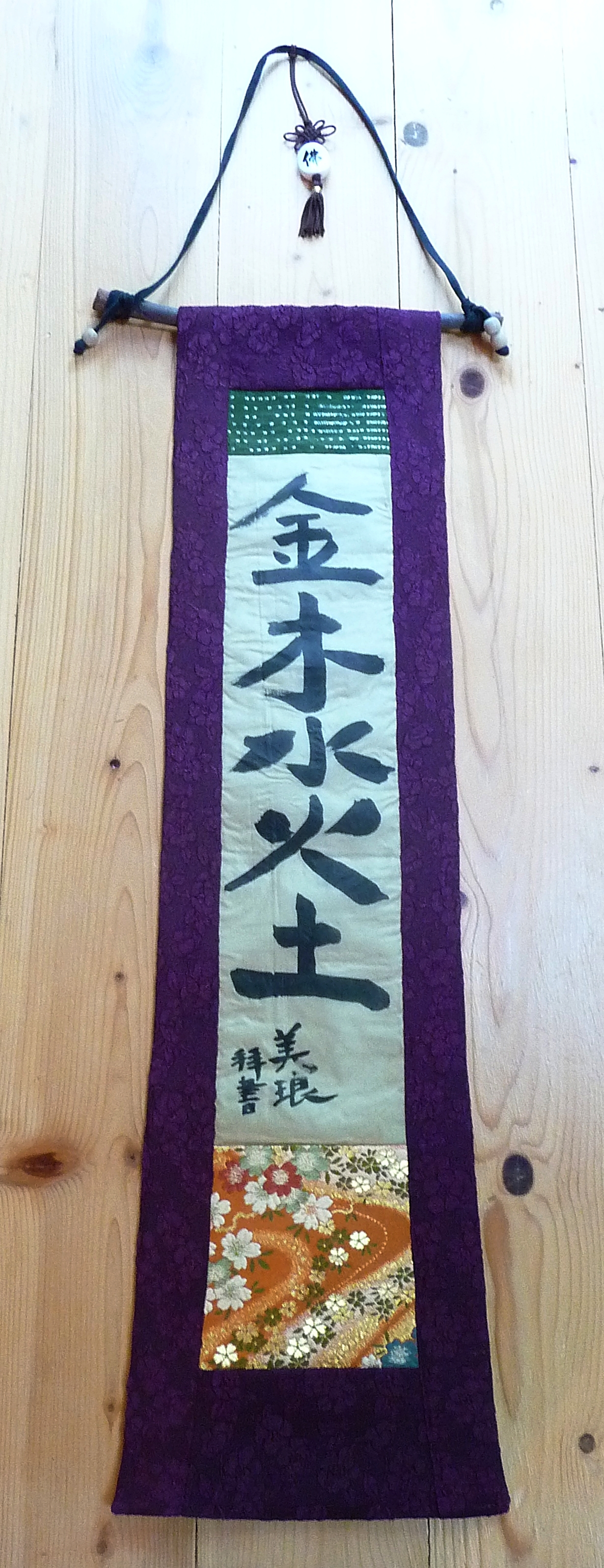 Calligraphy framed in purple silk, accented by sari fabric and Japanese brocade