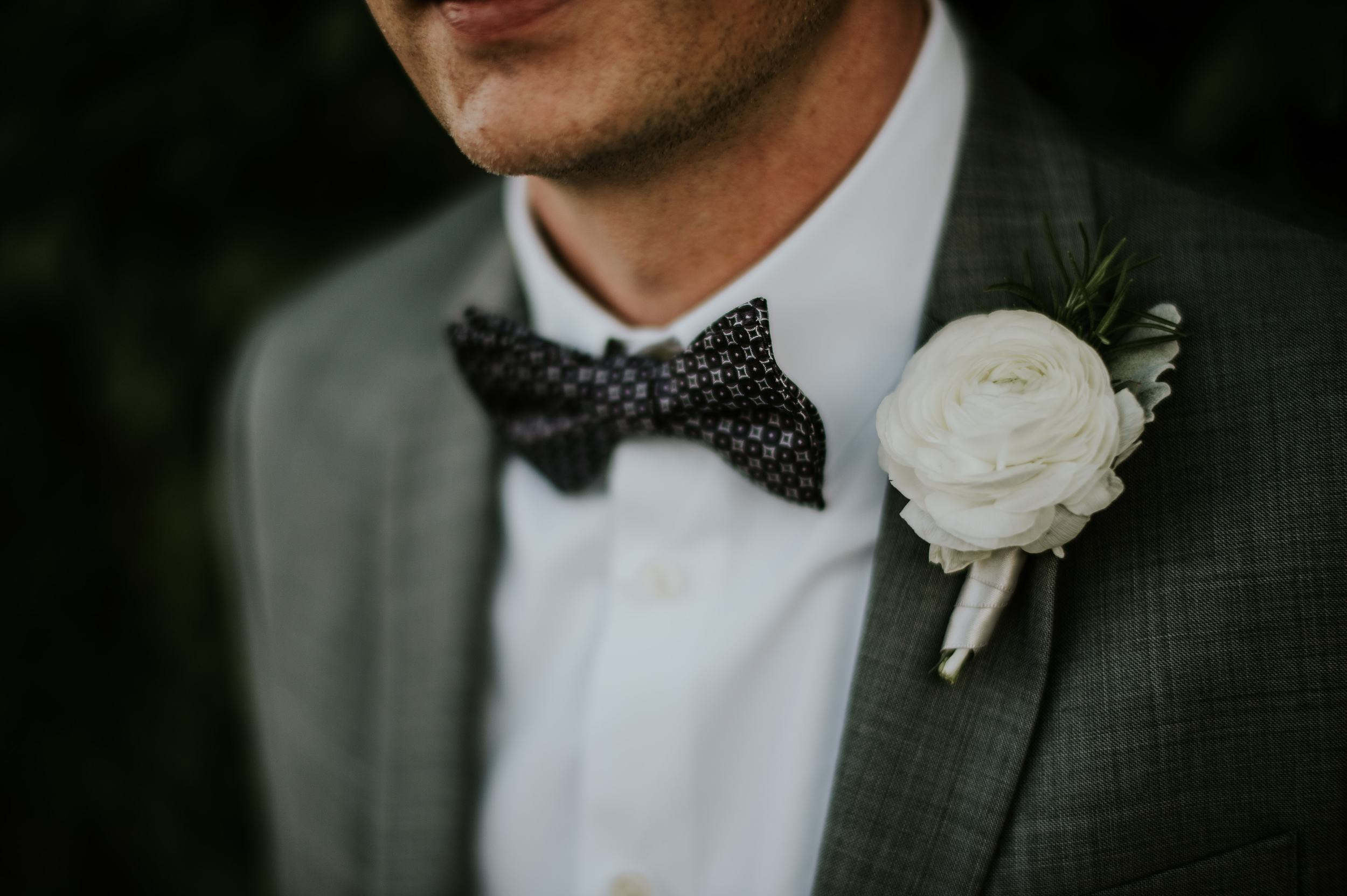 Adam's simple white ranunculus boutonniere with rosemary was the perfect detail!