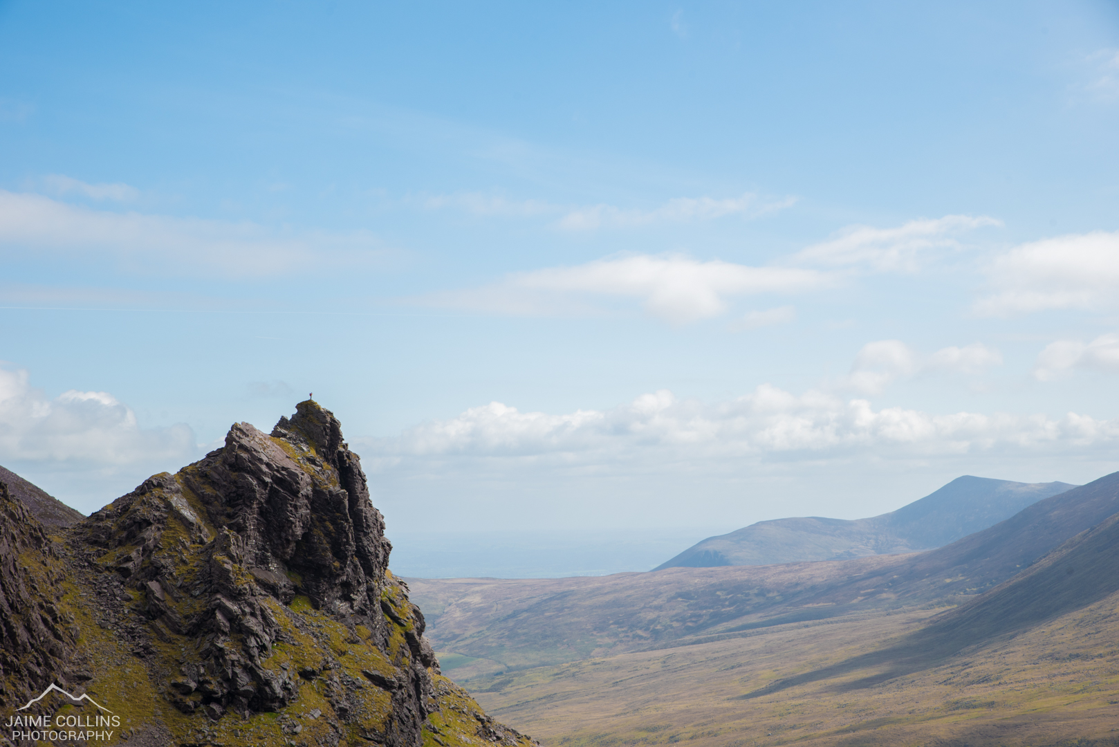 A lone hiker standing on top of a rock outcrop