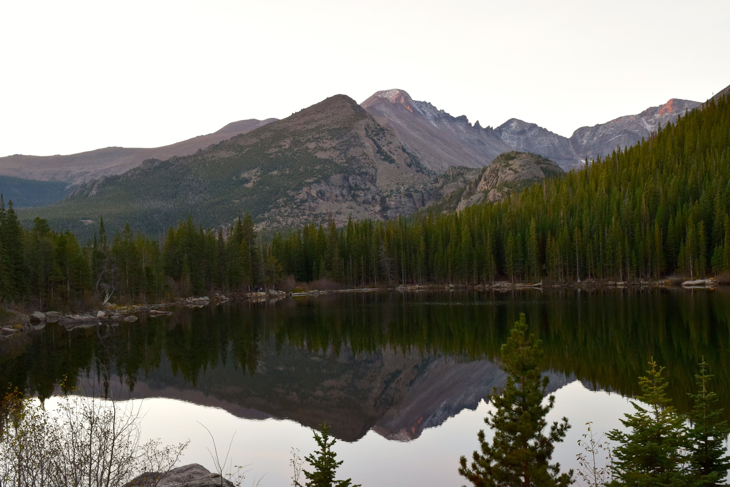 Golden hour lighting, alpenglow on the distant mountains, and a perfectly still lake.