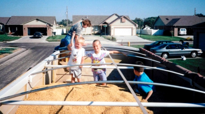 Playing in a truckload of soybeans with Aunt Sue, cousin Trent, and brother Ray, circa 1998