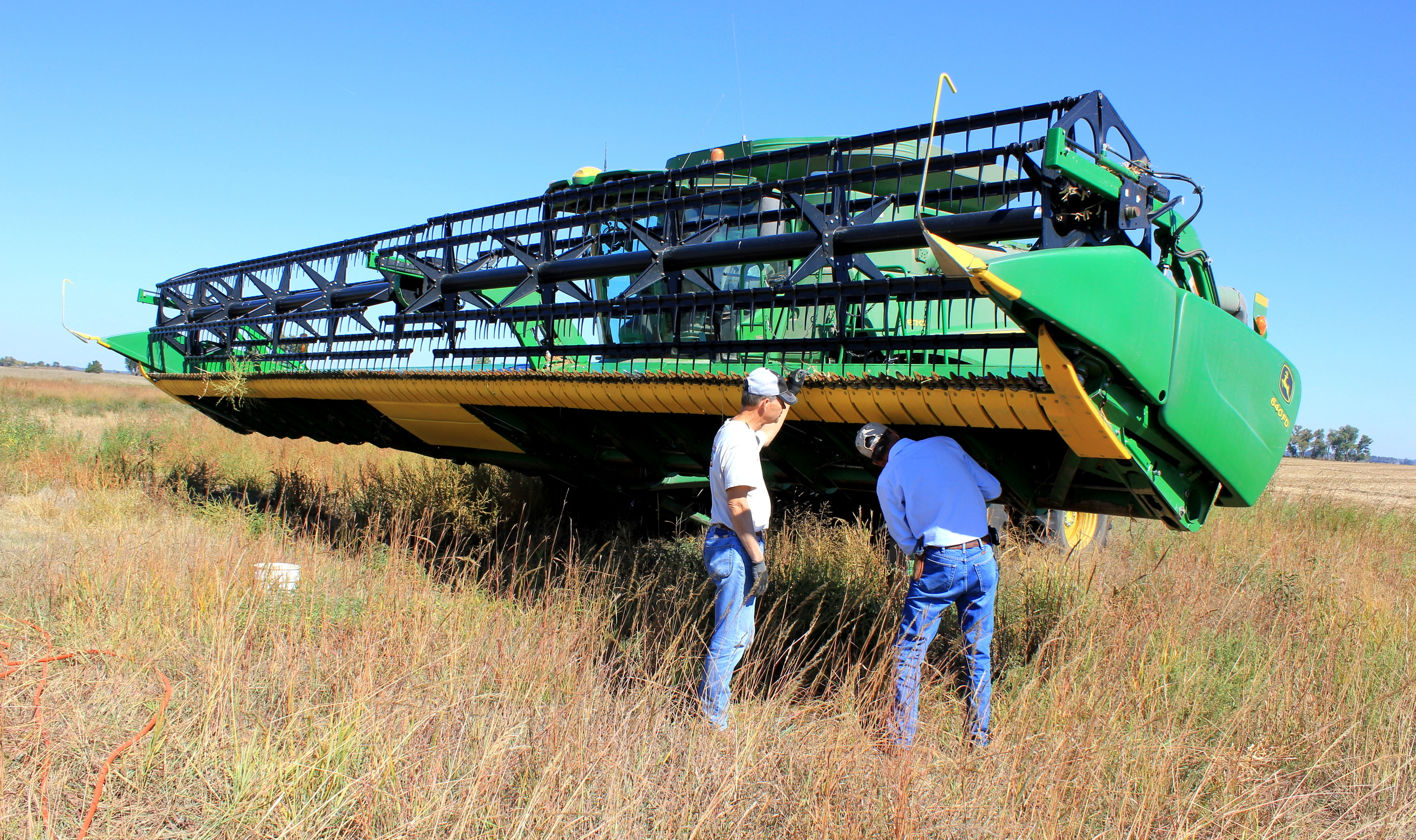 Dad and Vince adjusting the header of the combine to harvest milo