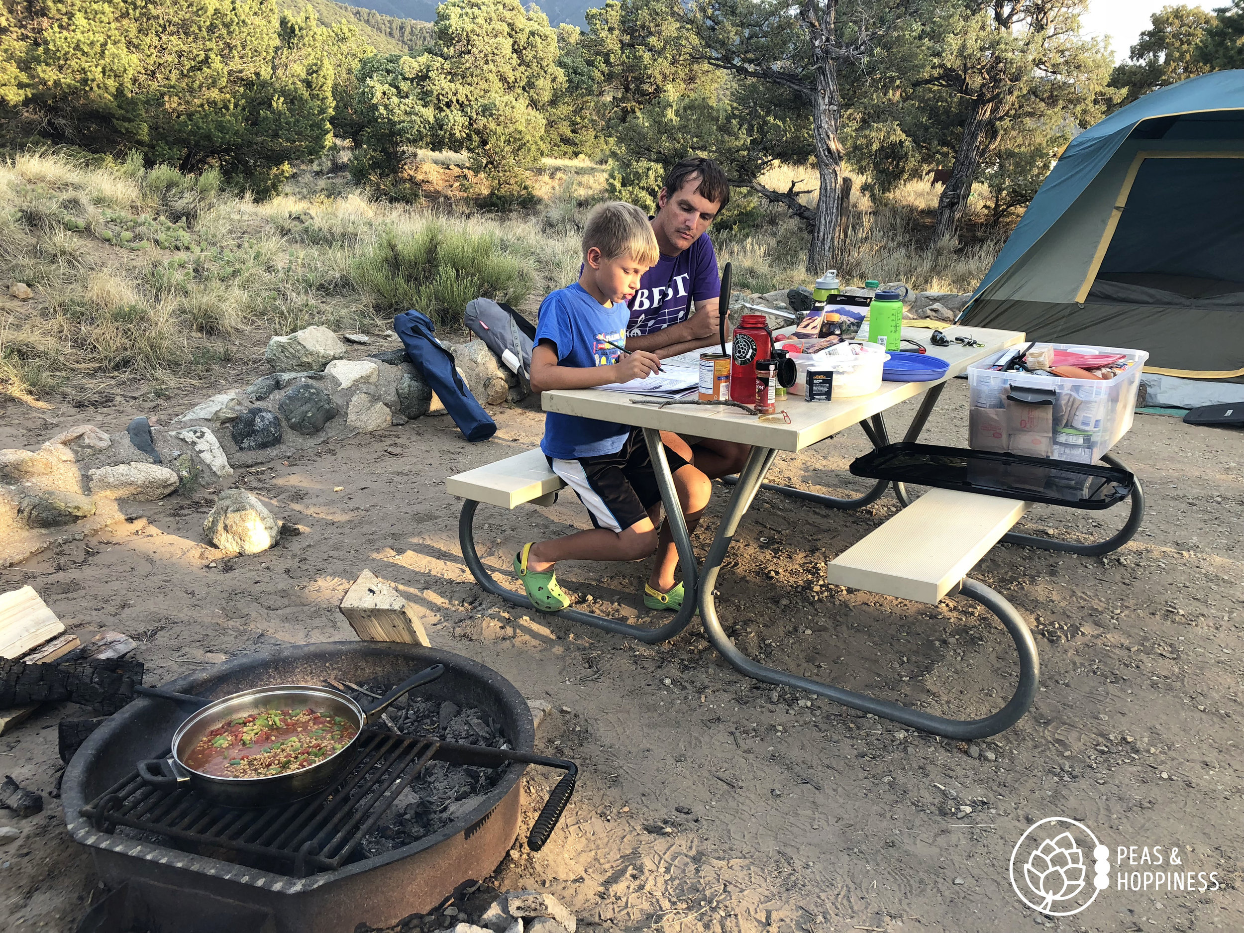 Working on Jonah's Junior Ranger book while Lentil Frito Pie cooks over the fire. Great Sand Dunes National Park.
