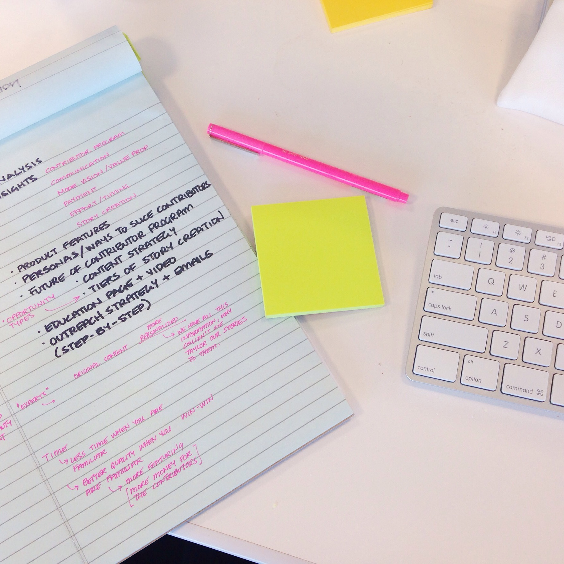 Notepad with post it note and keyboard.