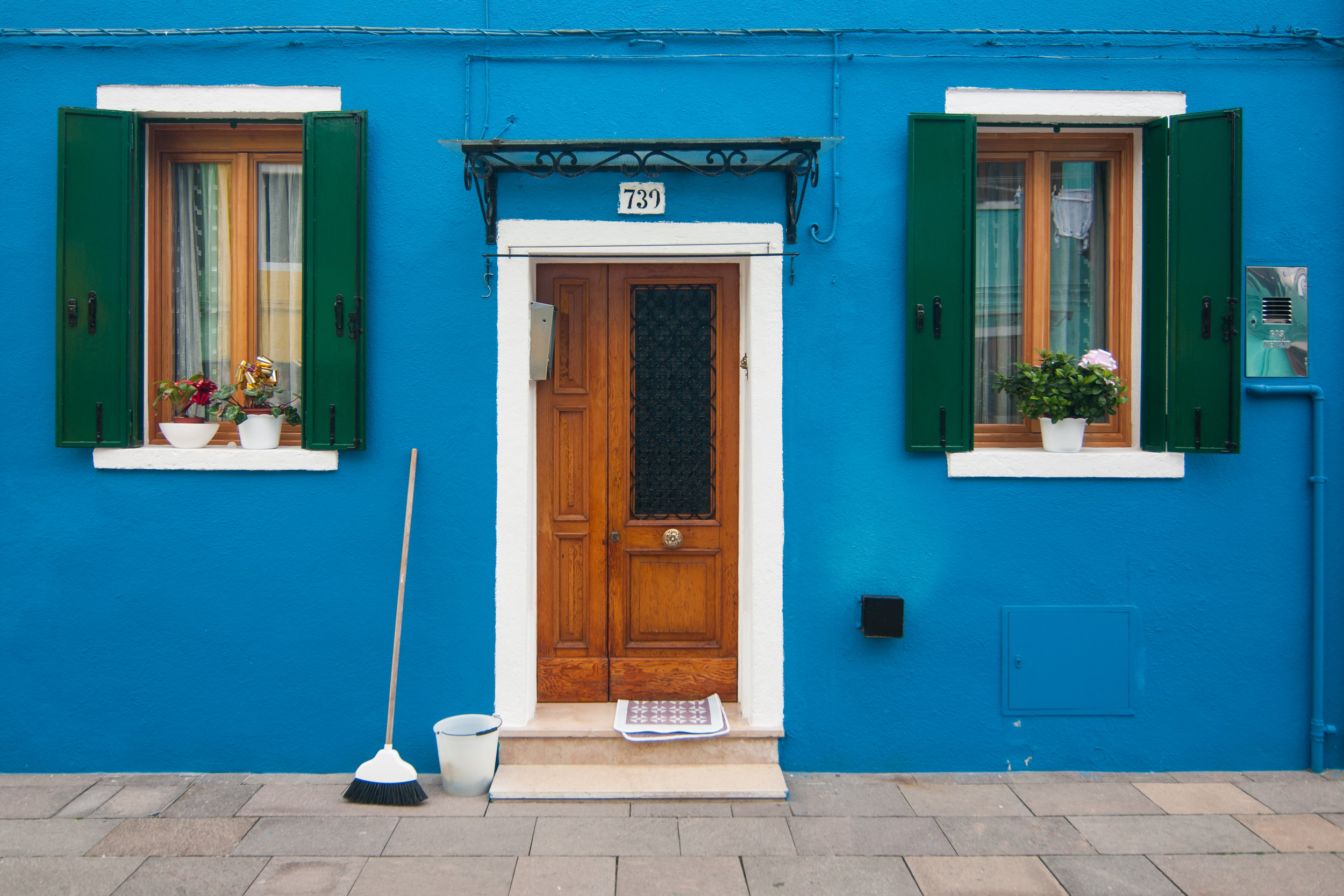 A blue house with a broom normally used to clean the front door of the houses in the island of Burano, Venice, Italy.