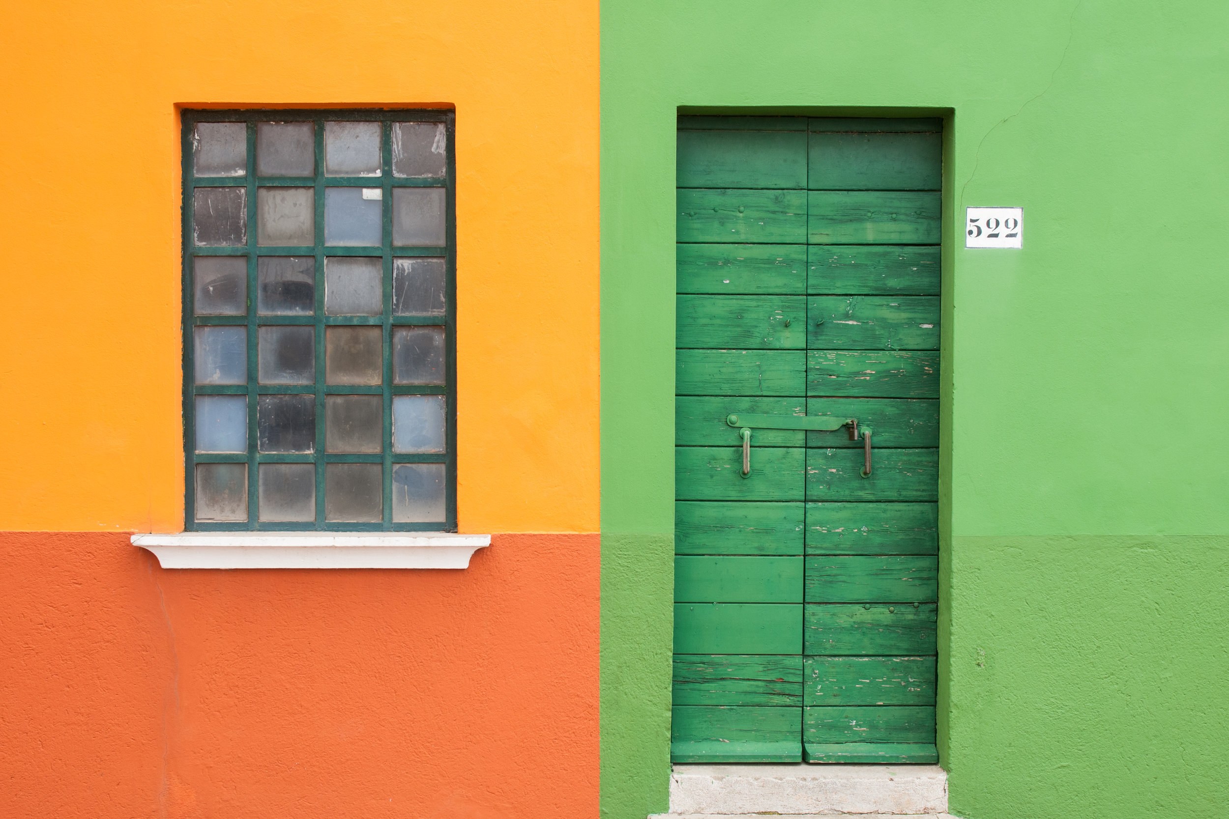 A window and a door on green, red and yellow wall in the island of Burano, Venice, Italy.