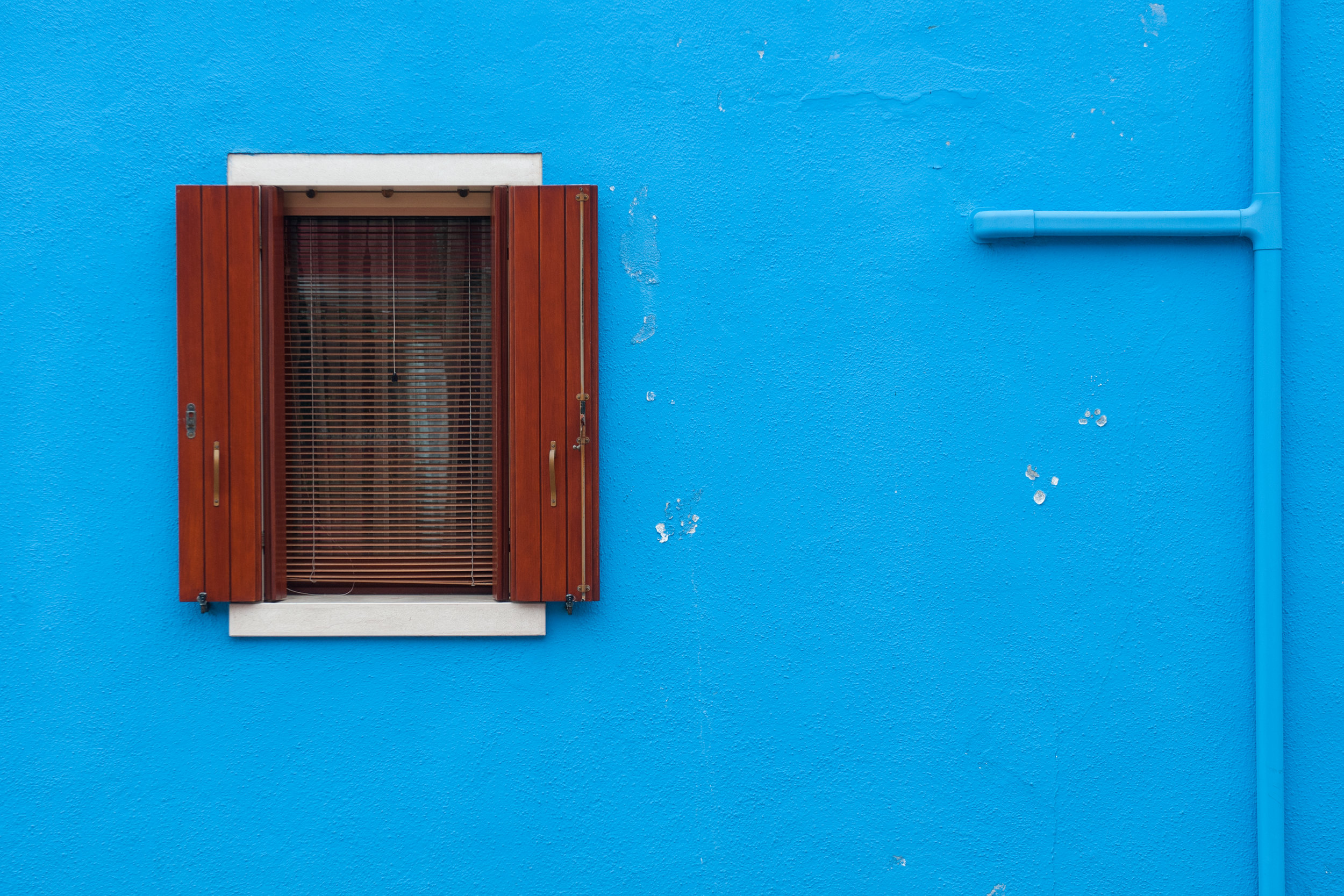 A window on a blue wall in the island of Burano, Venice, Italy.