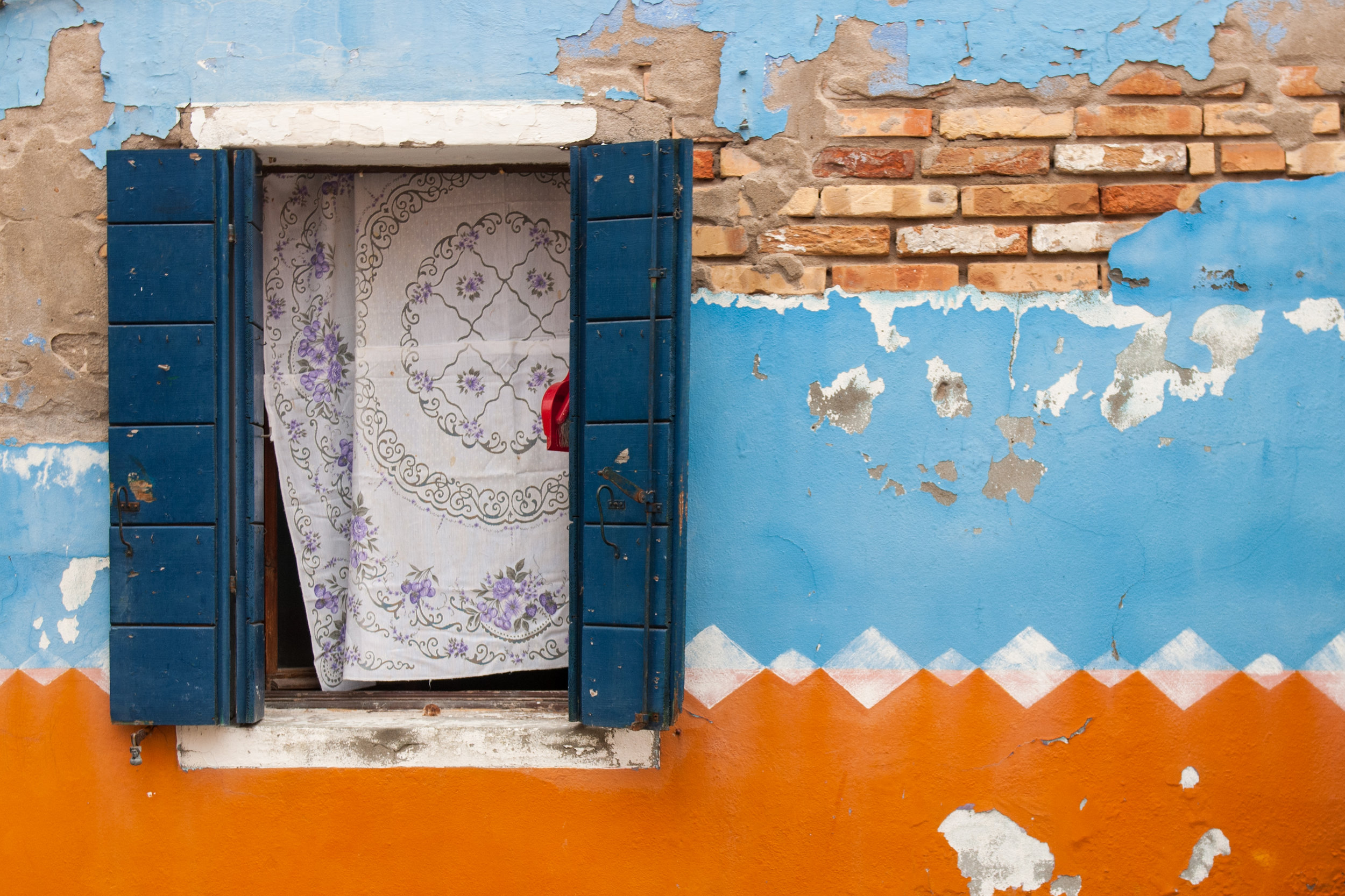 A blue window on an orange and ble wall in the island of Burano, Venice, Italy.